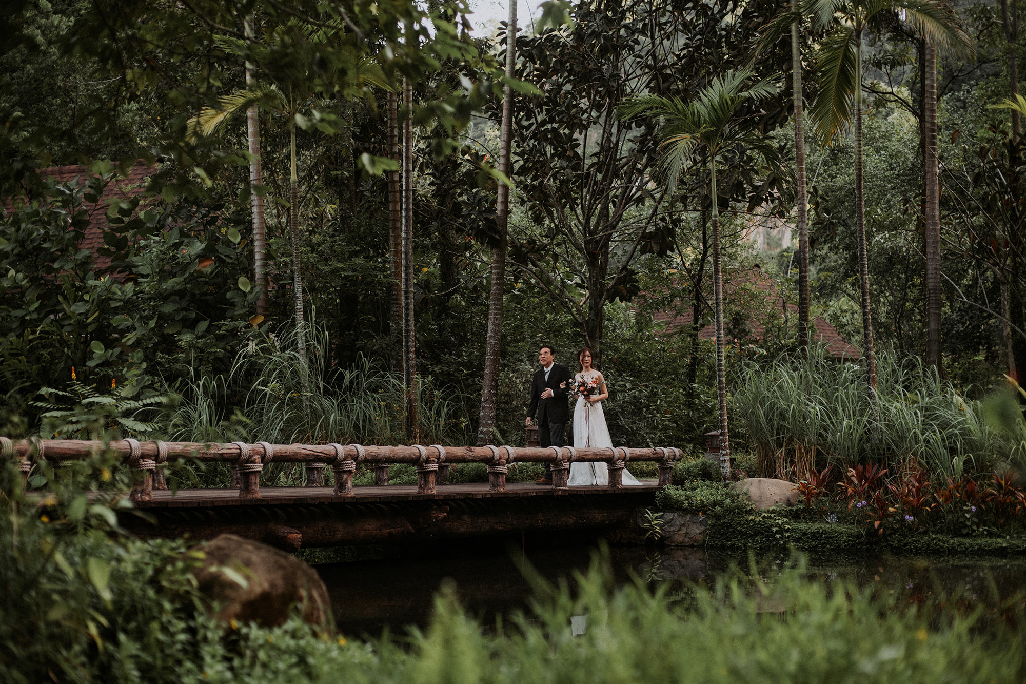Bride and dad walking on bridge in Malaysian jungle.