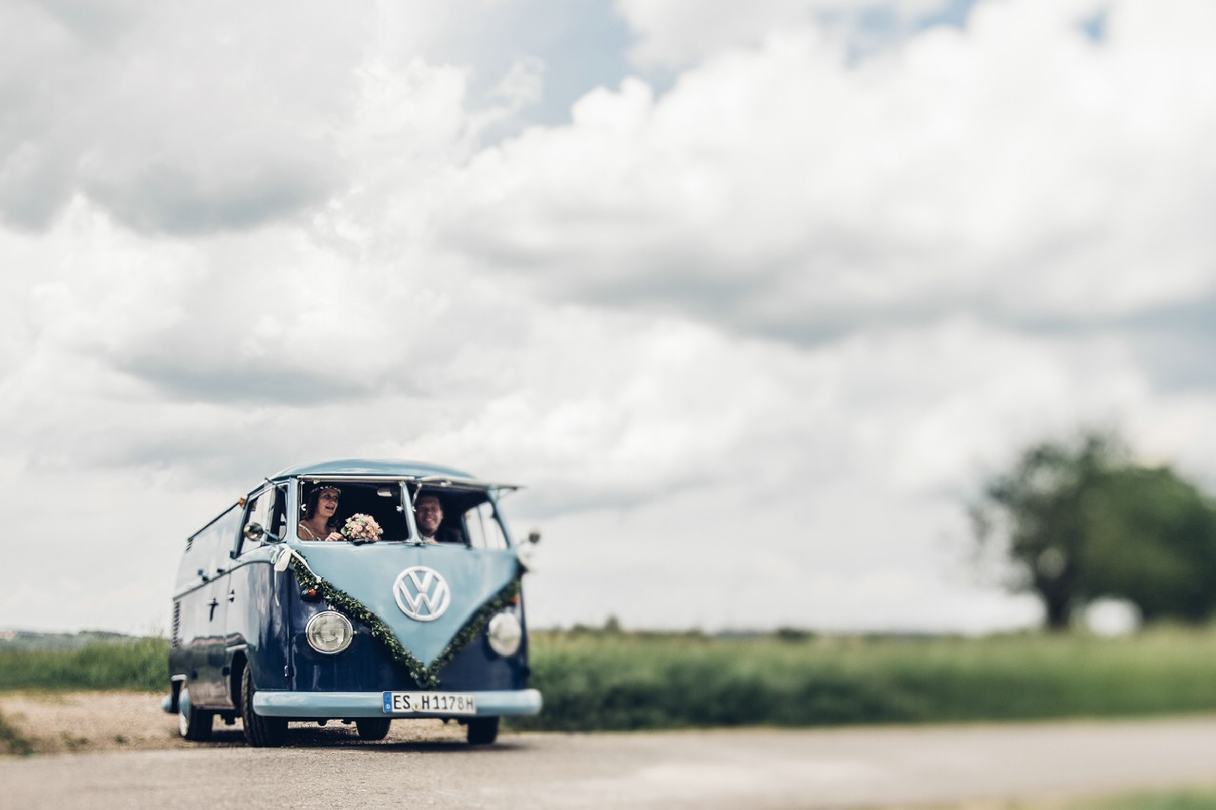 ​​​​Couple leaves wedding ceremony in blue Volkswagen Bus - photo by Fine-art Weddings Photography Germany