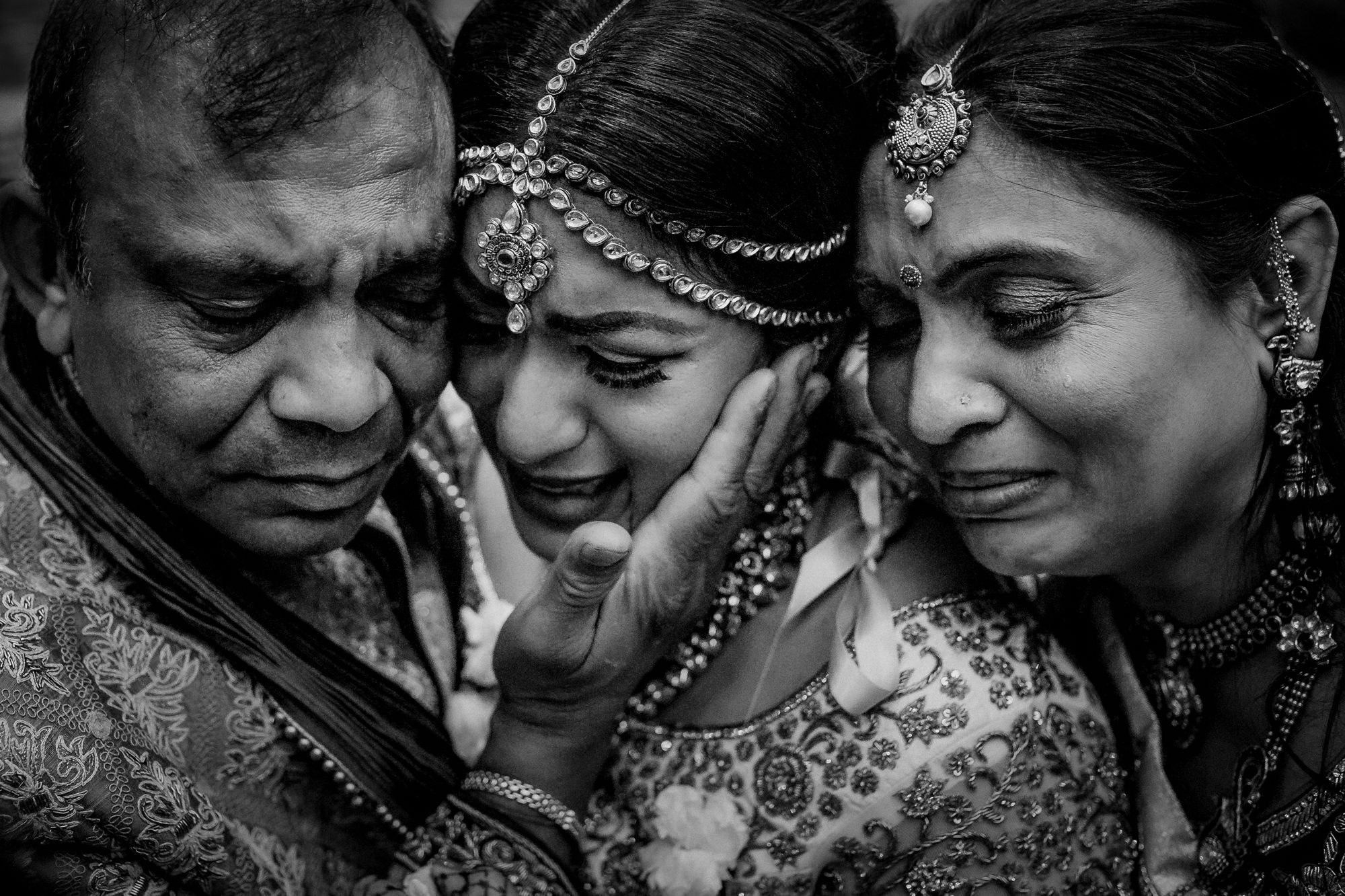 Indian bride embracing mom and dad in emotional moment by Matei Horvath of Los Angeles