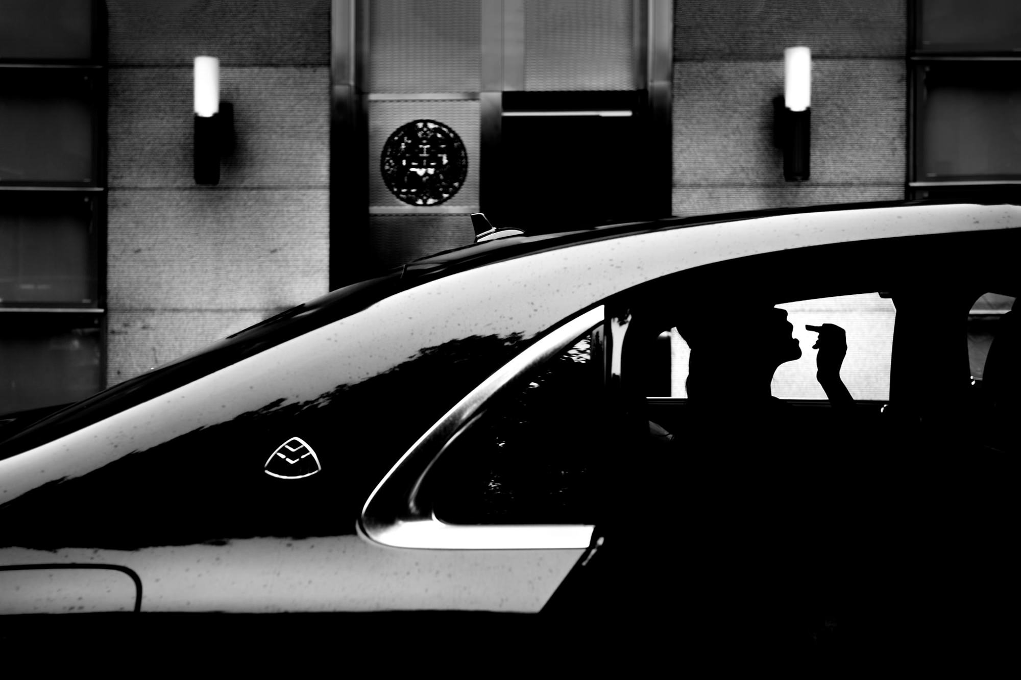 Silhouette of bride applying lipstick in limo - photo by Two Mann Studios