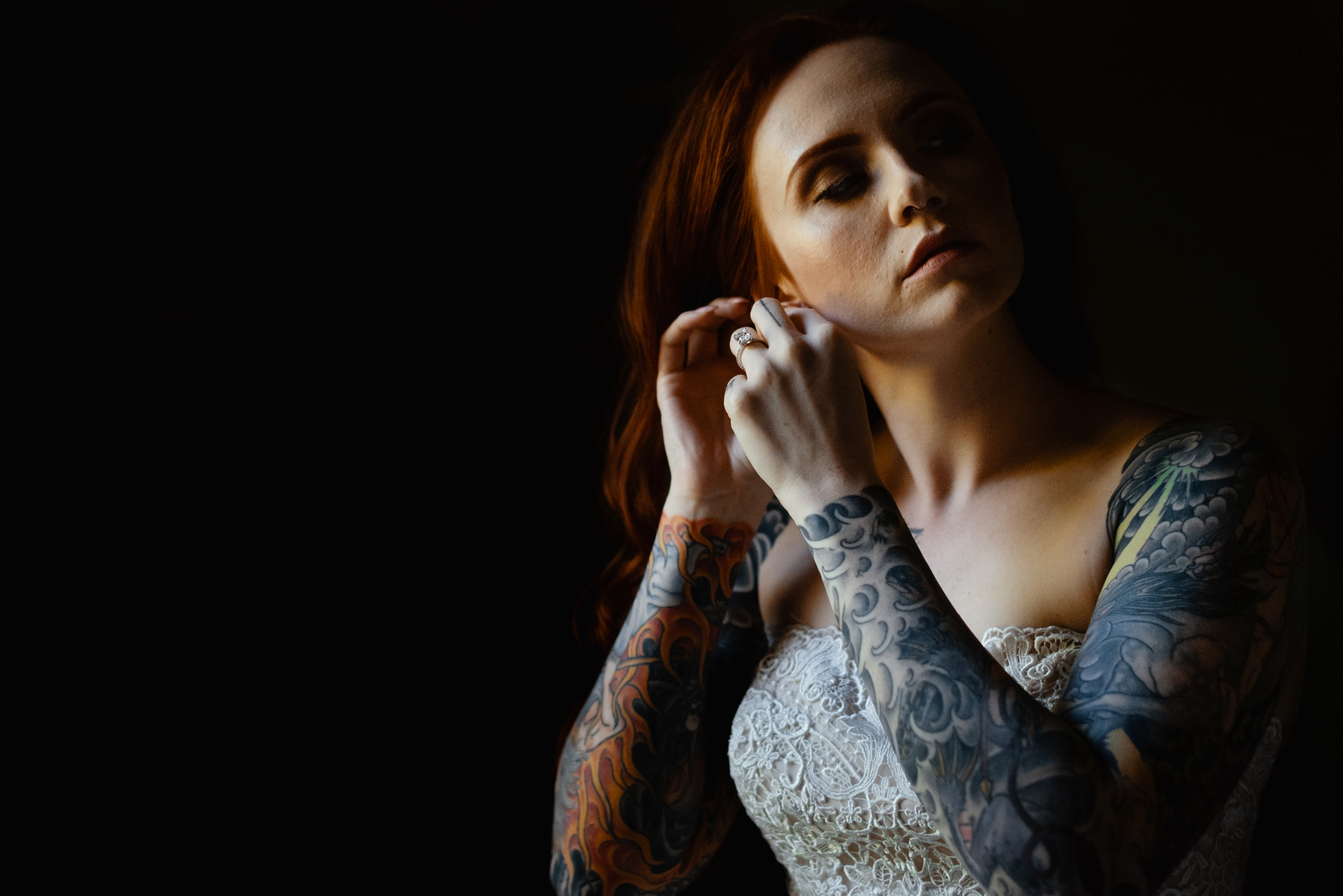 bride-with-intricate-tattoos-putting-her-earrings-on-new-orleans-austin-houston-wedding-photo-by-dark-roux
