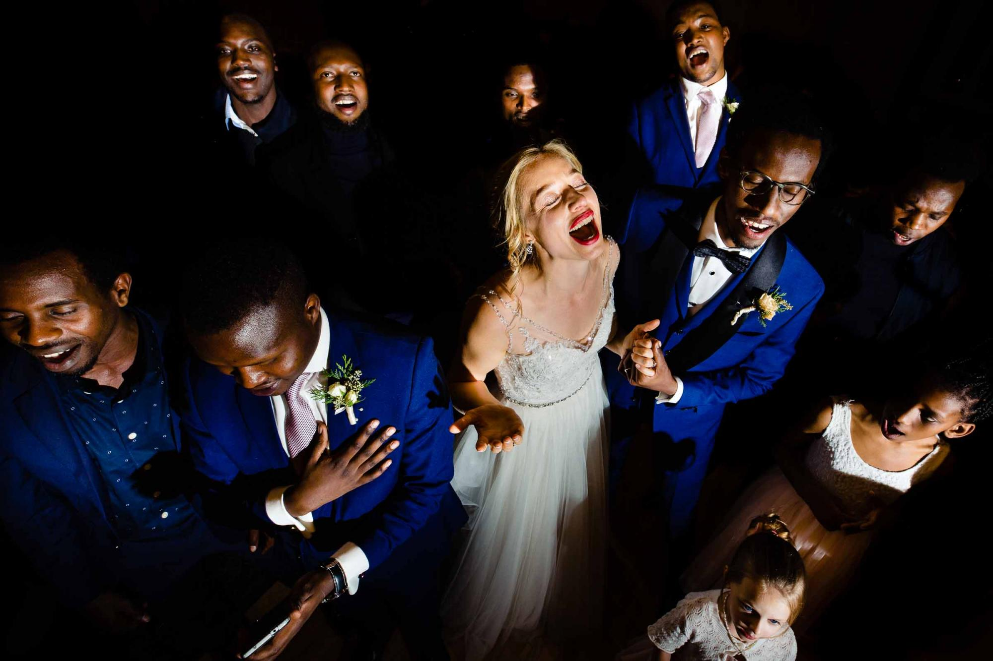 Bride singing with joy surrounded by a choir of friends photographed by Jos & Tree