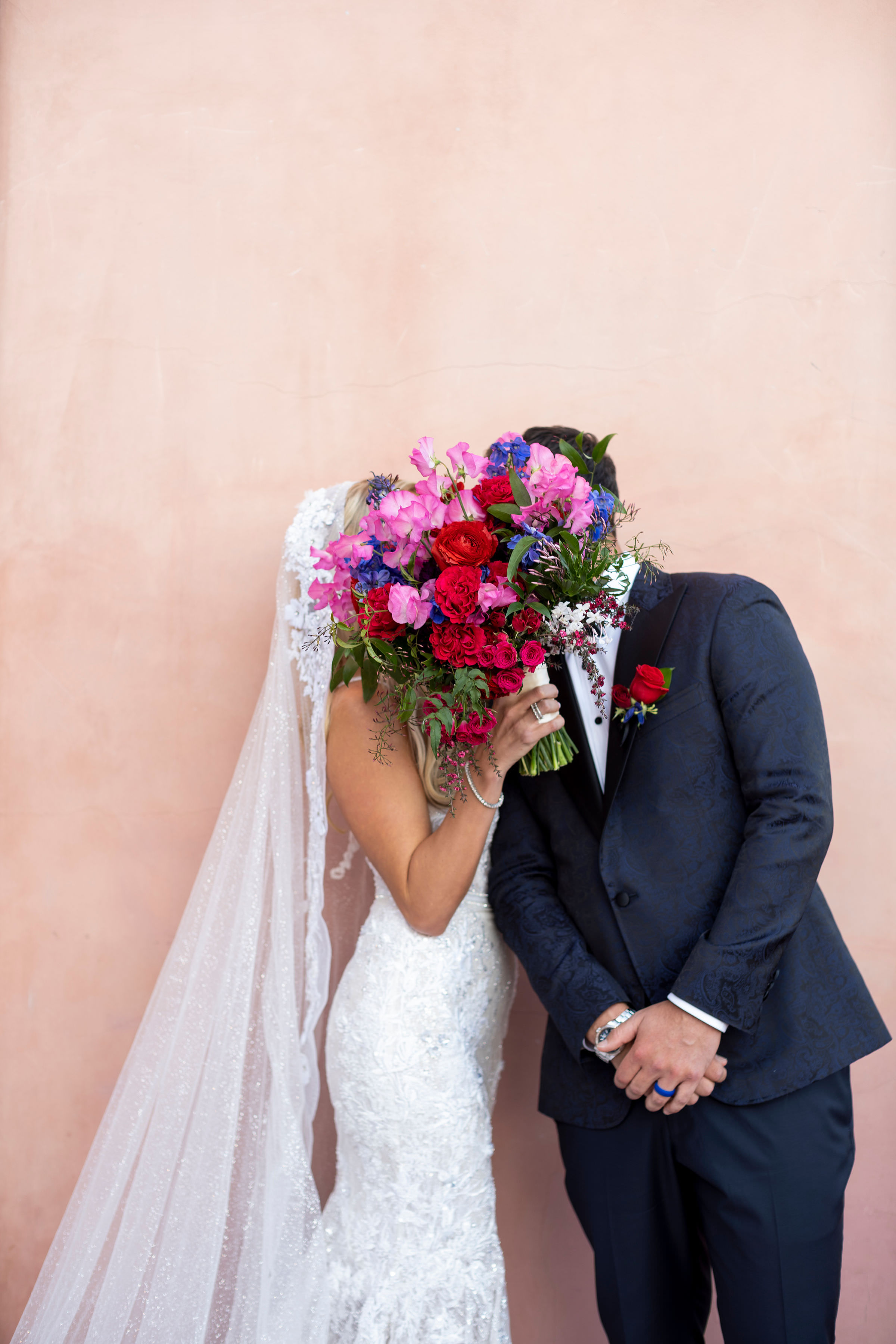 couple-kisses-behind-red-rose-and-pink-sweet-pea-bouquet--john-joseph
