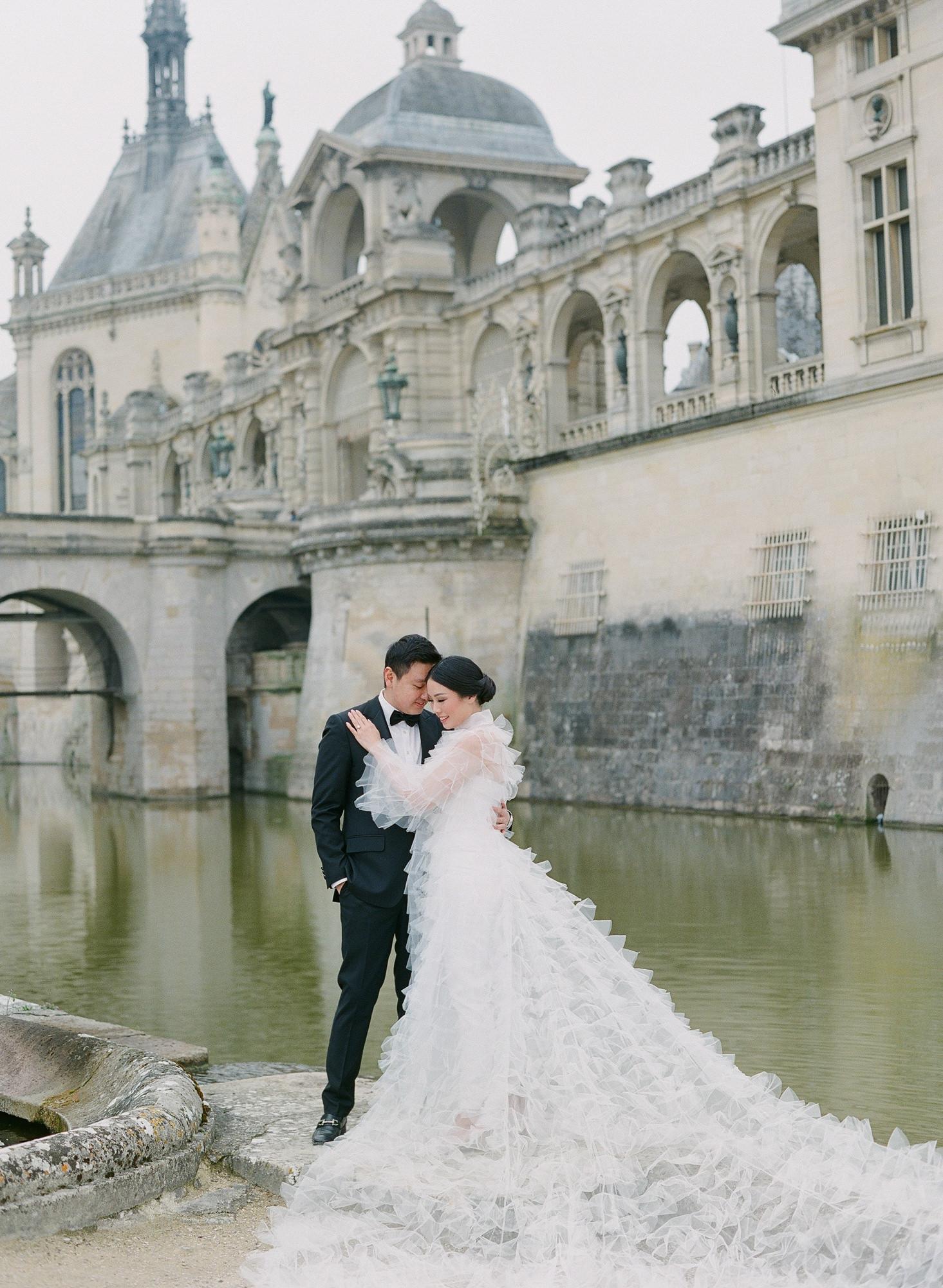 elegant-asian-couple-by-river-paris-long-sleeve-white-ruffled-coat-worlds-best-wedding-photos-greg-finck-france-wedding-photographers