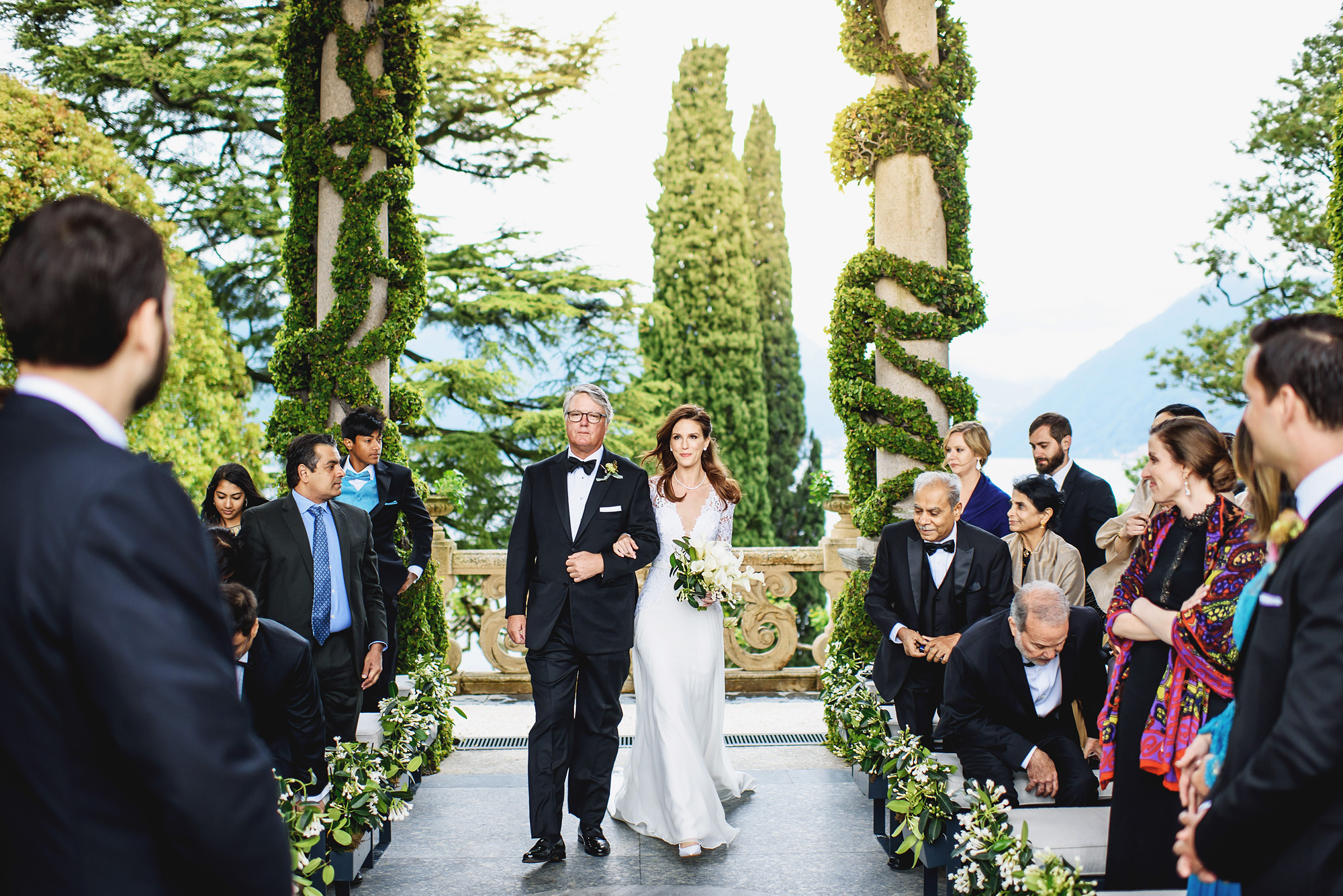 father-and-bride-come-down-the-asile-lake-como-weddding-worlds-best-photos-ross-harvey-london