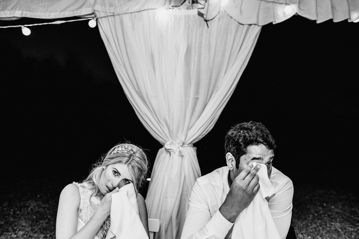 Couple crying into serviettes at wedding table photographed by Samo Rovan