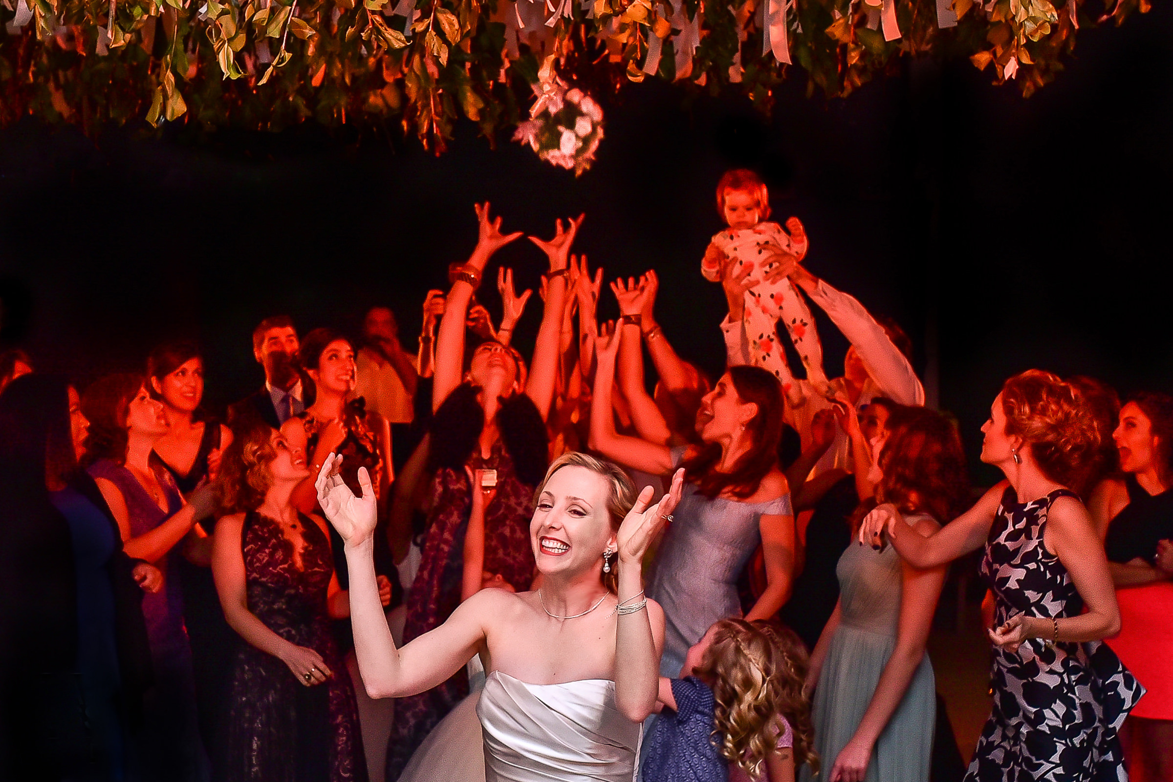Happy bride throwing her bouquet to guests on dance floor - Car & Mel Photography - Mexico wedding photographers