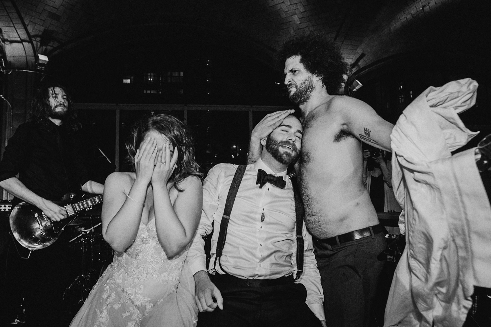 black-and-white-topless-guest-pressing-groom-head-onto-chest-worlds-best-wedding-photos-dan-o-day-australia-wedding-photographer