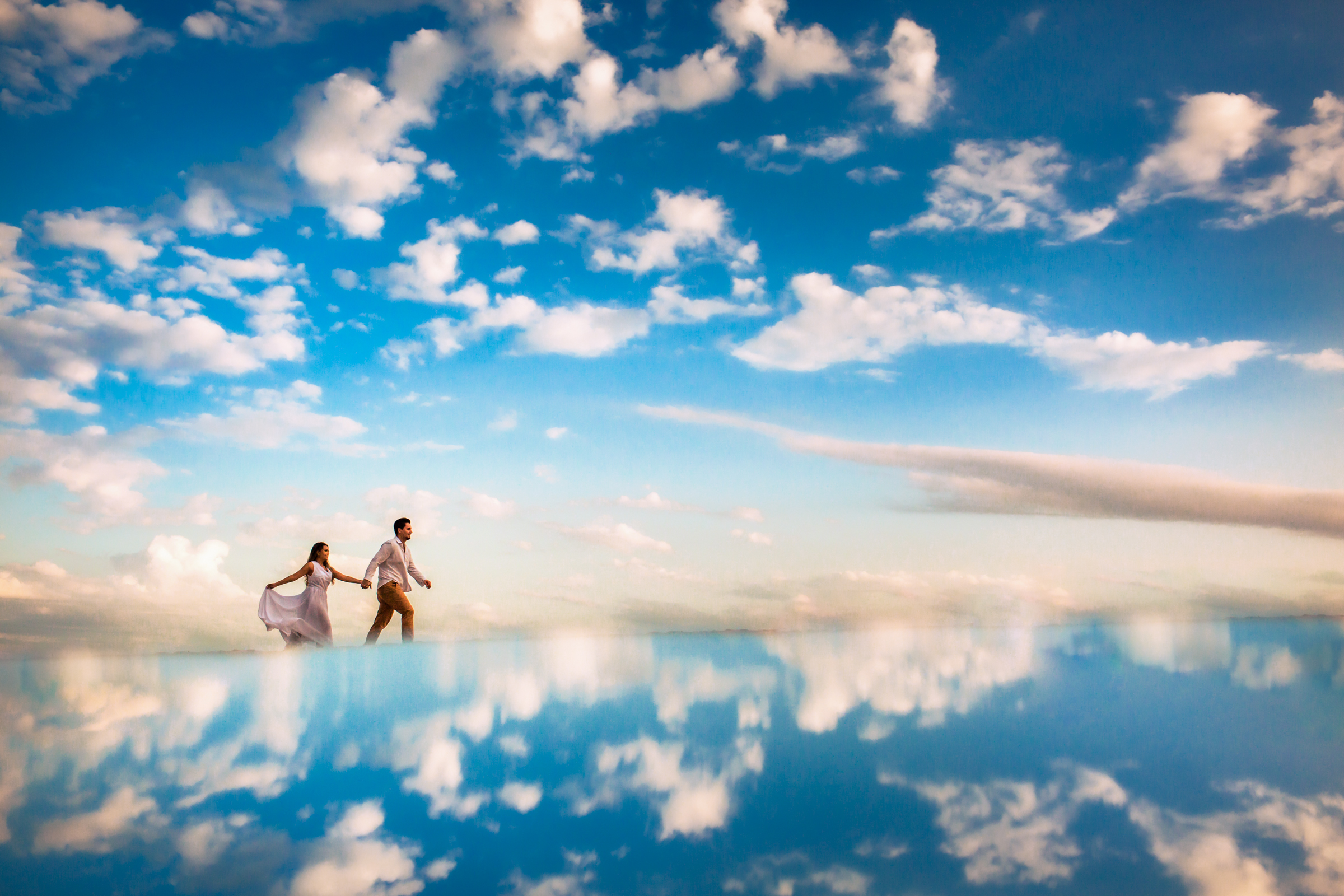 couple-walking-on-clouds-in-blue-sky-area-da-fotografia