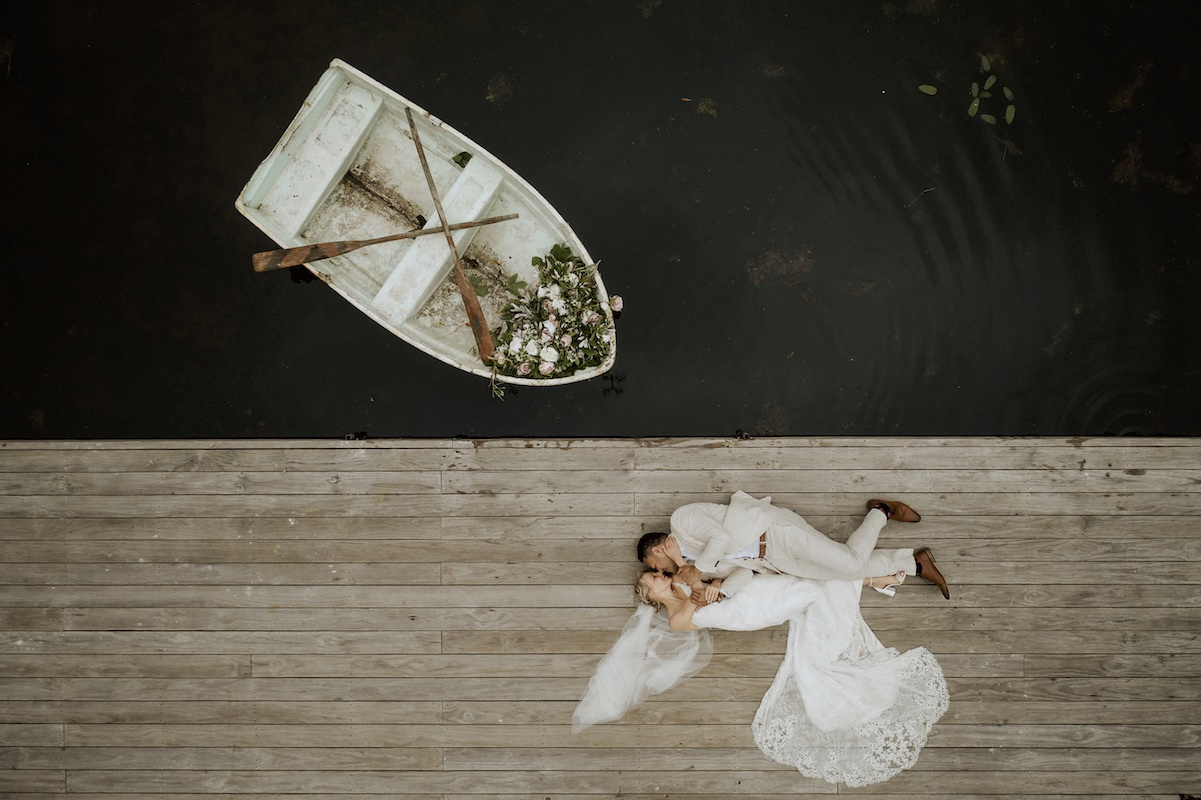 couple-laying-on-dock-next-to-rowboat-full-of-flowers-two-little-starfish-new-zealand