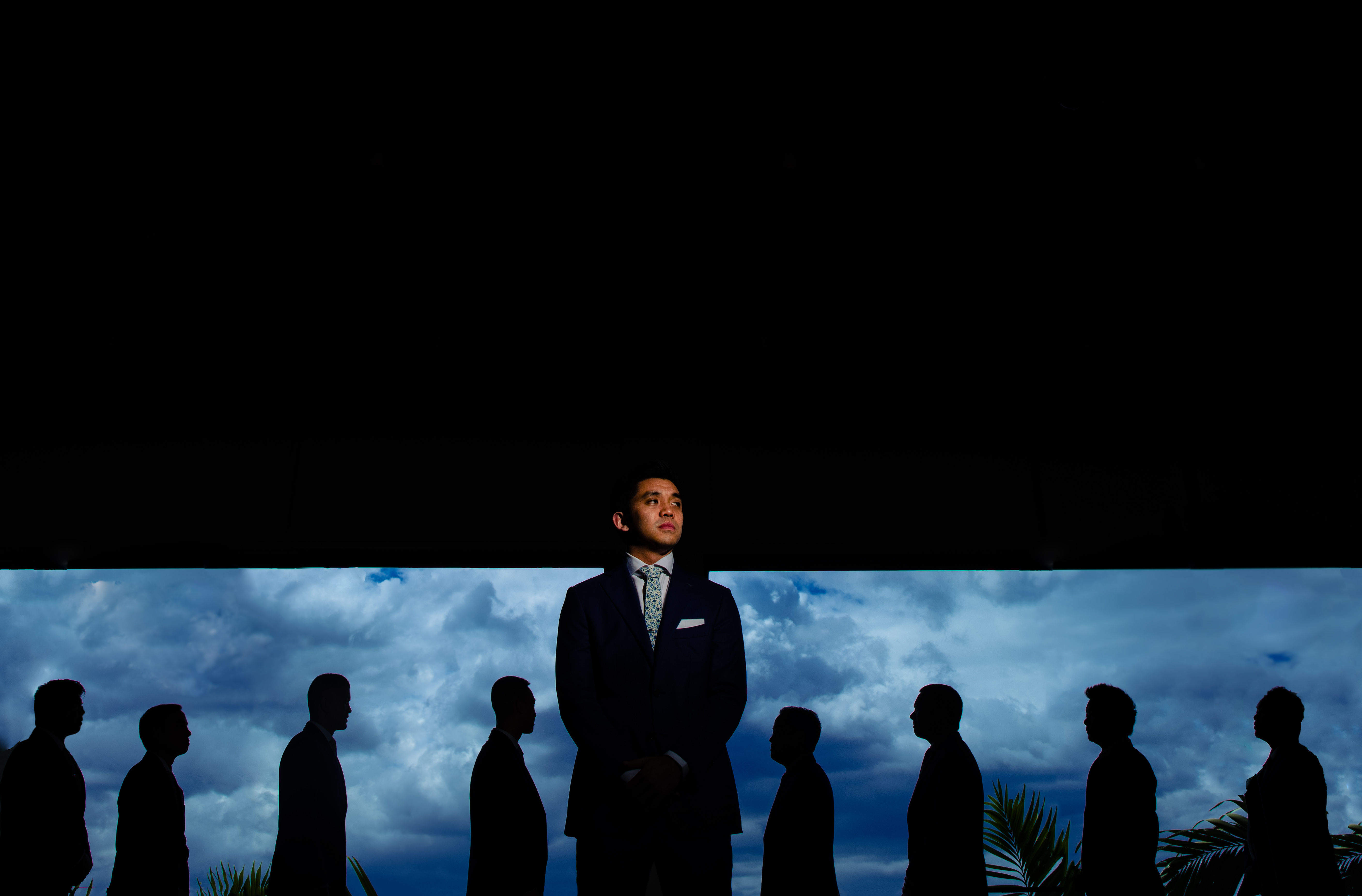 groom-against-silhouette-groomsmen-and-sky-by-angela-nelson-photography