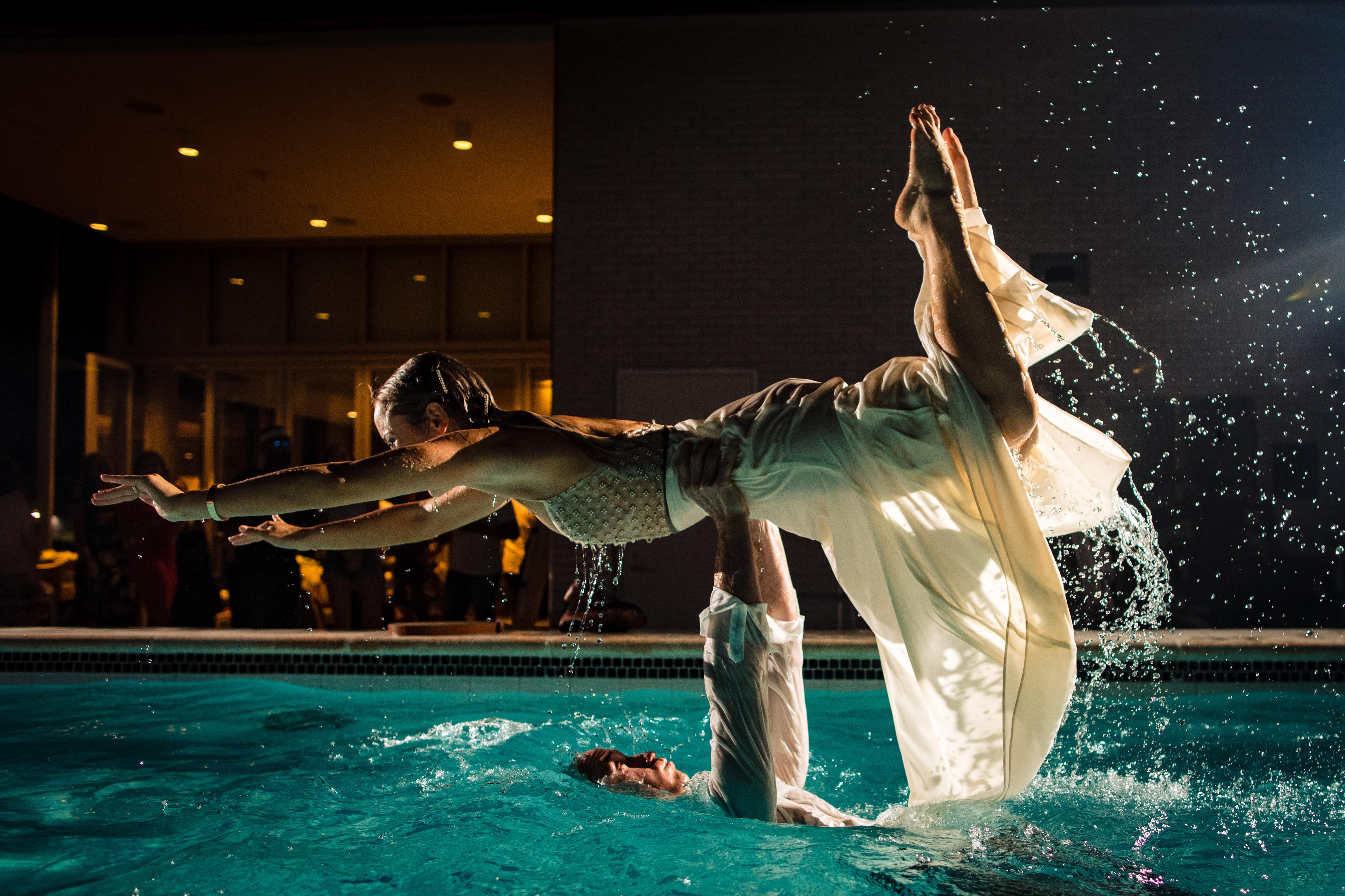 groom-lifts-bride-horizontally-in-nighttime-pool-so-tender-is-humanity