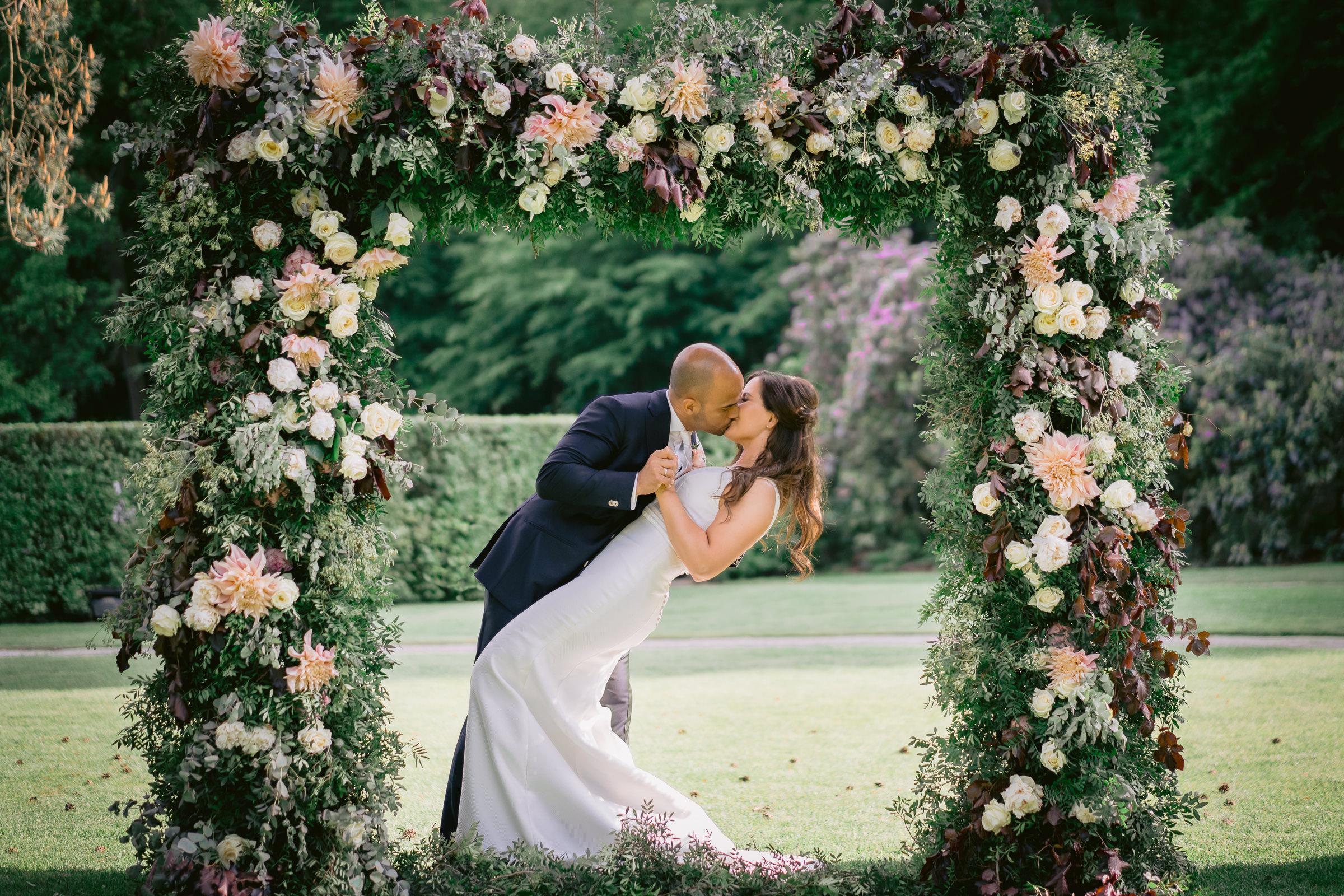 portrait-of-groom-kissing-bride-under-floral-arbor-peter-van-der-lingen-wedding-photography