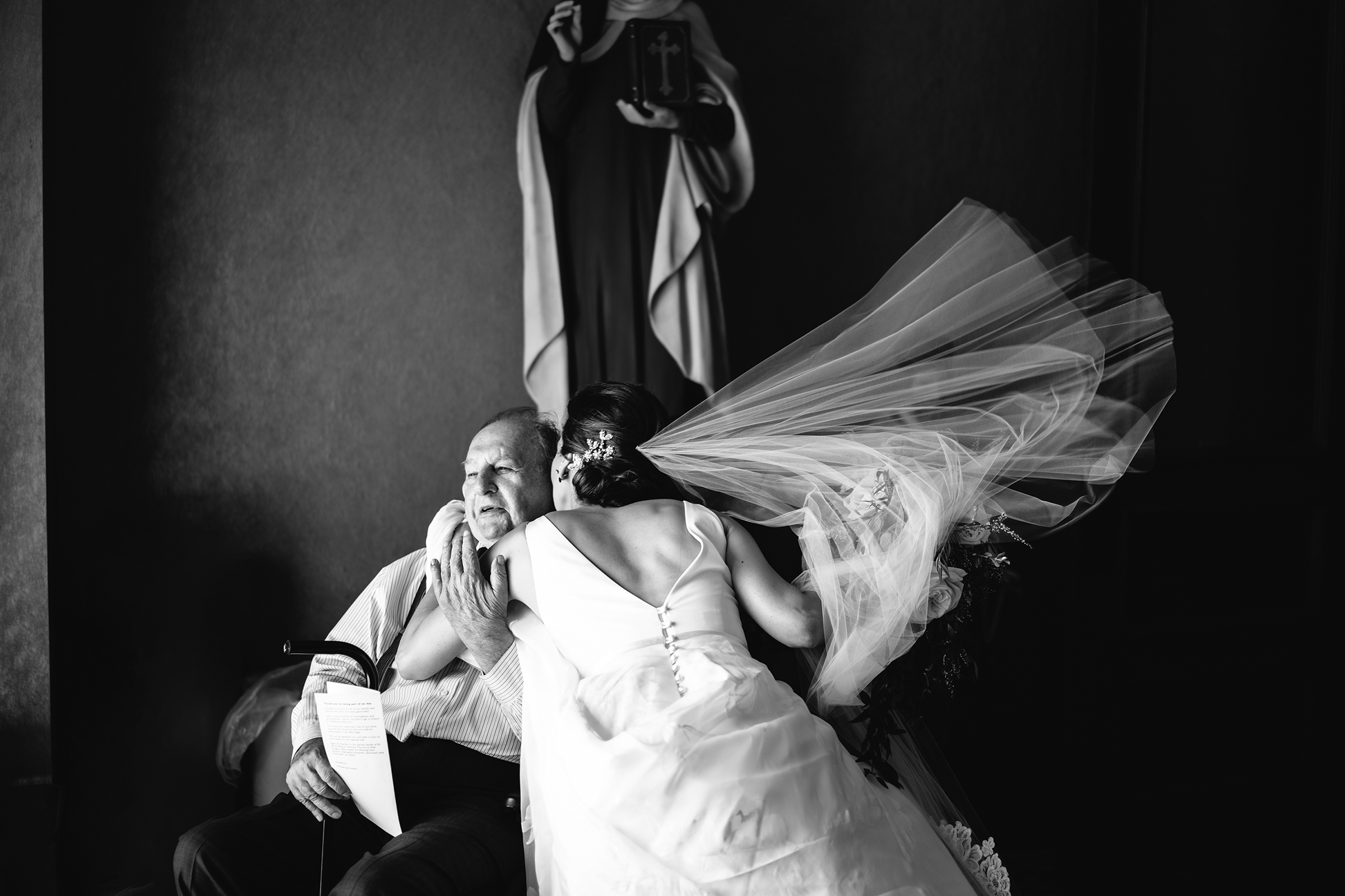 bride-in-flying-embrace-of-seated-grandfather-bradley-hanson-photography