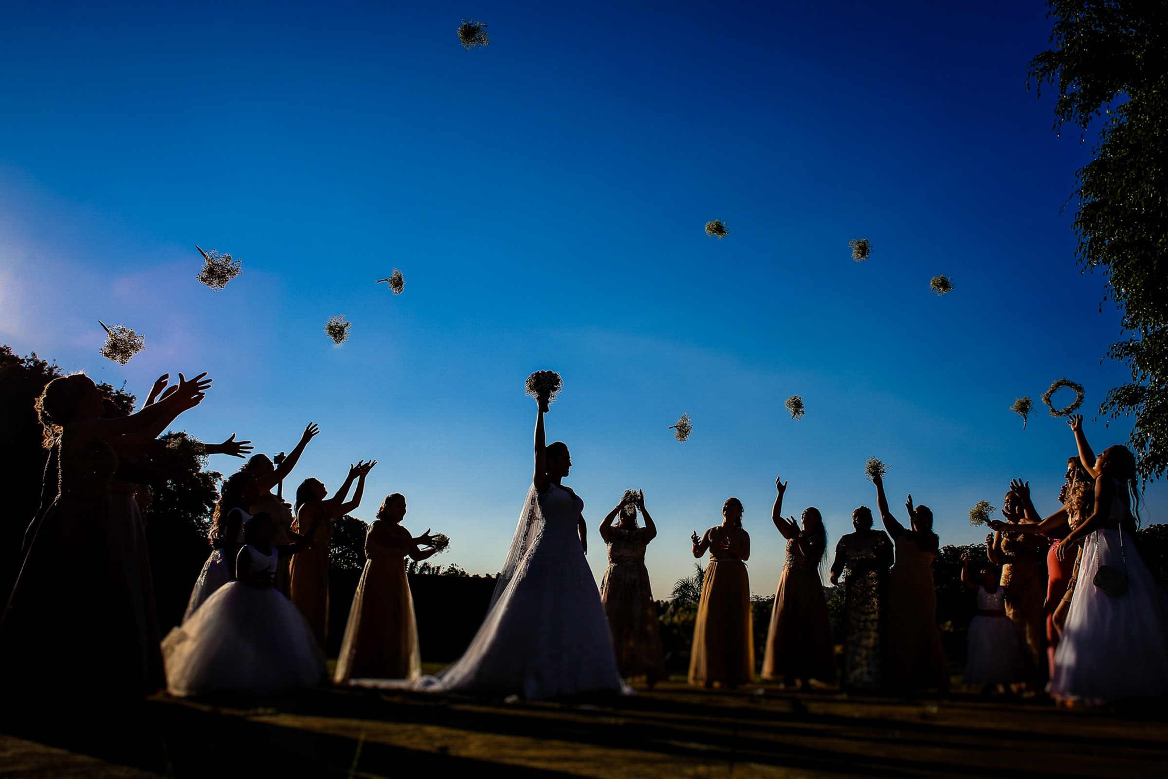 Silhouette of bride and bridesmaid holding bouquets in the air - photo by Area da Fotografia - Brazil wedding photographers
