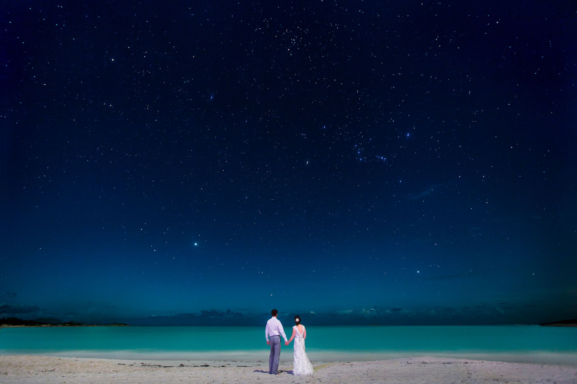 bride-and-groom-looks-out-at-the-stars-from-aqua-water-beach-worlds-best-wedding-photos-two-mann-studio-canada