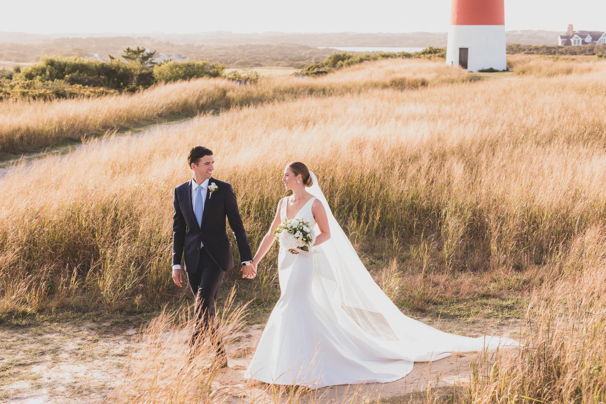 hand-in-hand-couple-in-grasses-against-lighthouse-katie-kaizer-photography