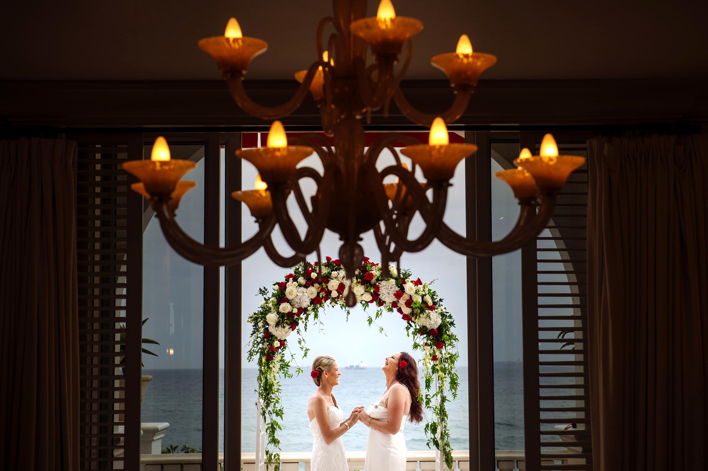 two-brides-celebrate-their-wedding-under-rose-arbor-jacki-bruniquel