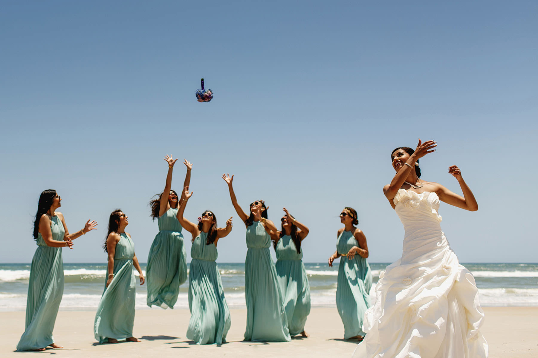 Bride tossing her bouquet on windy beach - photo by f5 Photography - UK wedding photographers