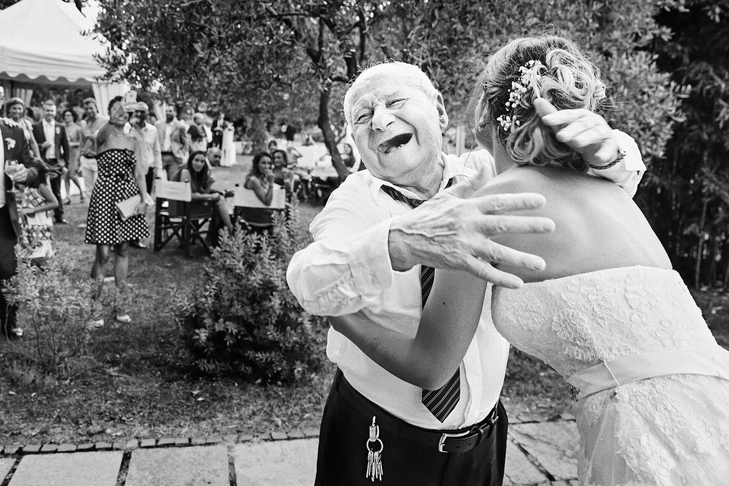 bride-embracing-laughing-grandfather-andrea-bagnasco-fotografie