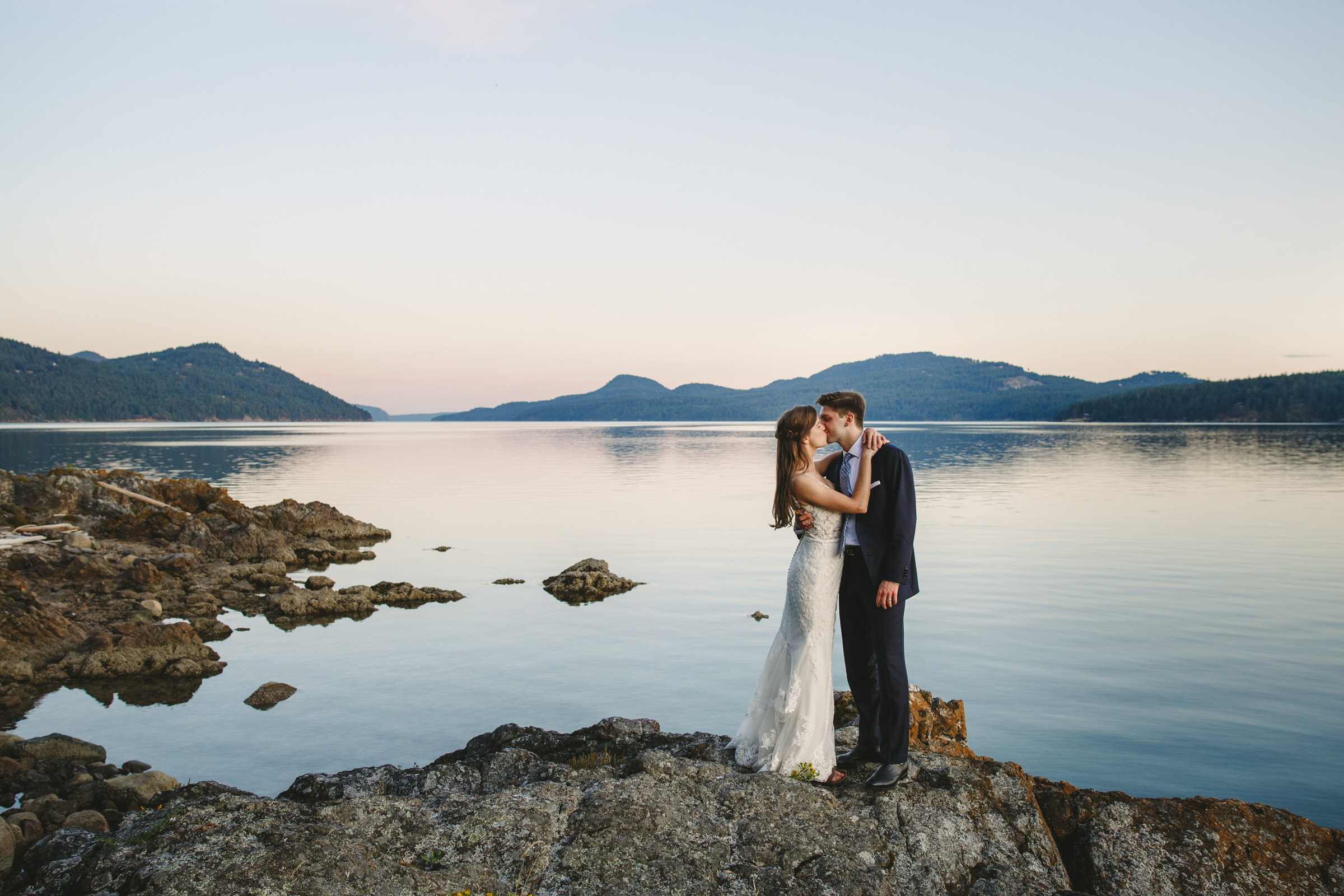 couple-kiss-on-shoreline-rocks-against-mountains-satya-curcio-photography