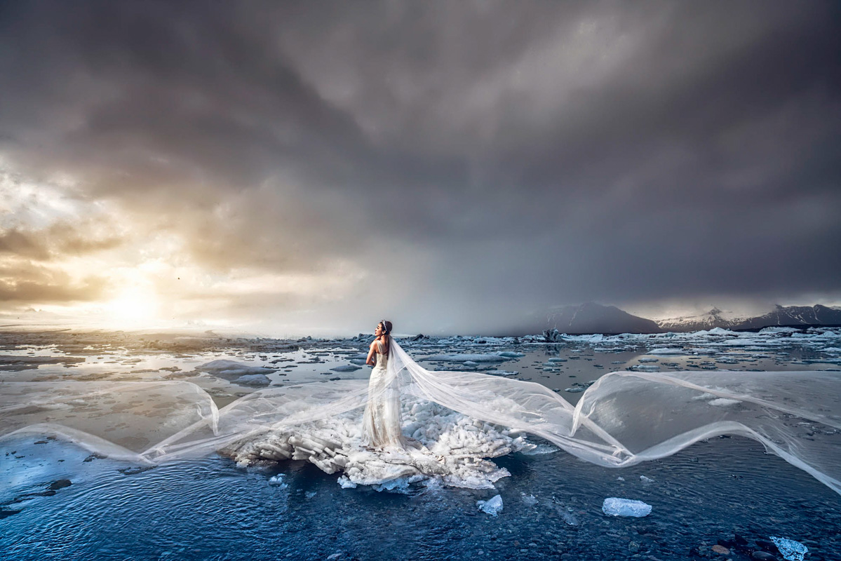 Dramatic photo of bride with long veil in ocean surf by CM Leung - Hong Kong