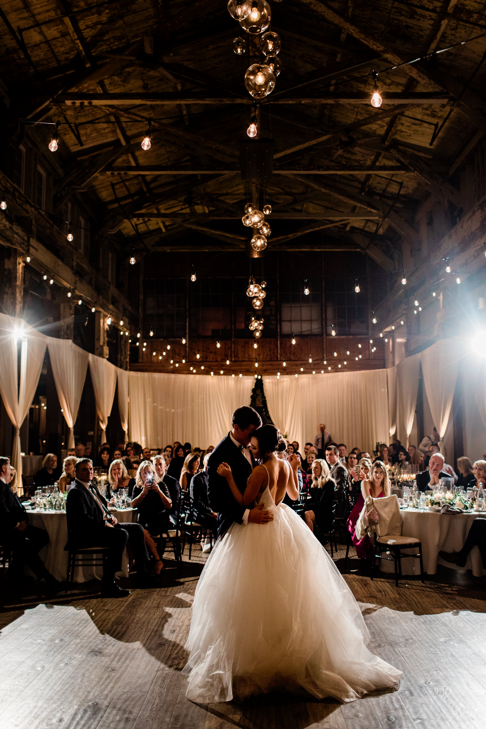 first-dance-at-evening-reception-under-strings-of-lights-against-white-drapery-into-dust-photography