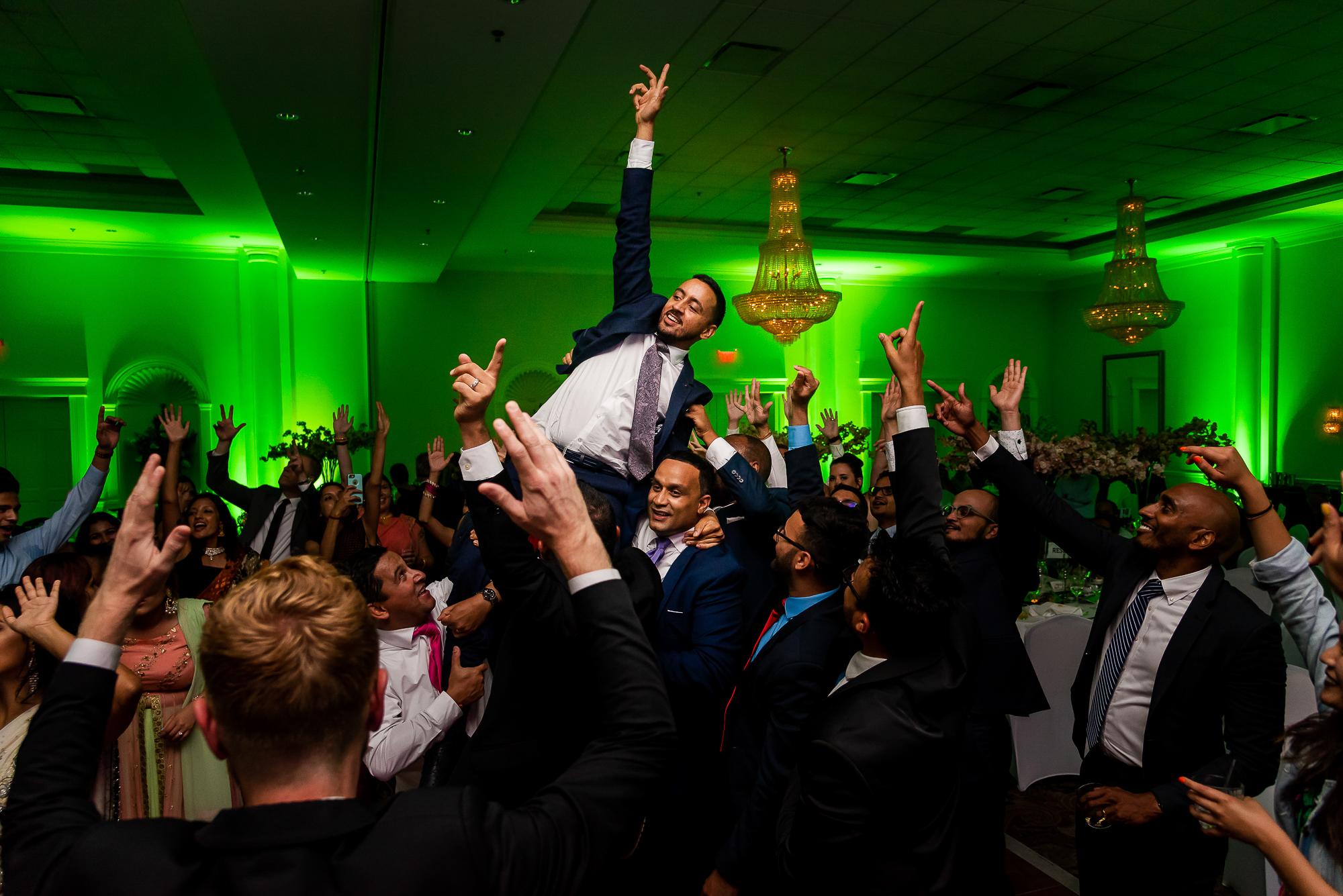 groom-raises-the-roof-on-shoulders-of-groomsmen-at-fox-chase-manor-christopher-jason-studios.jpg