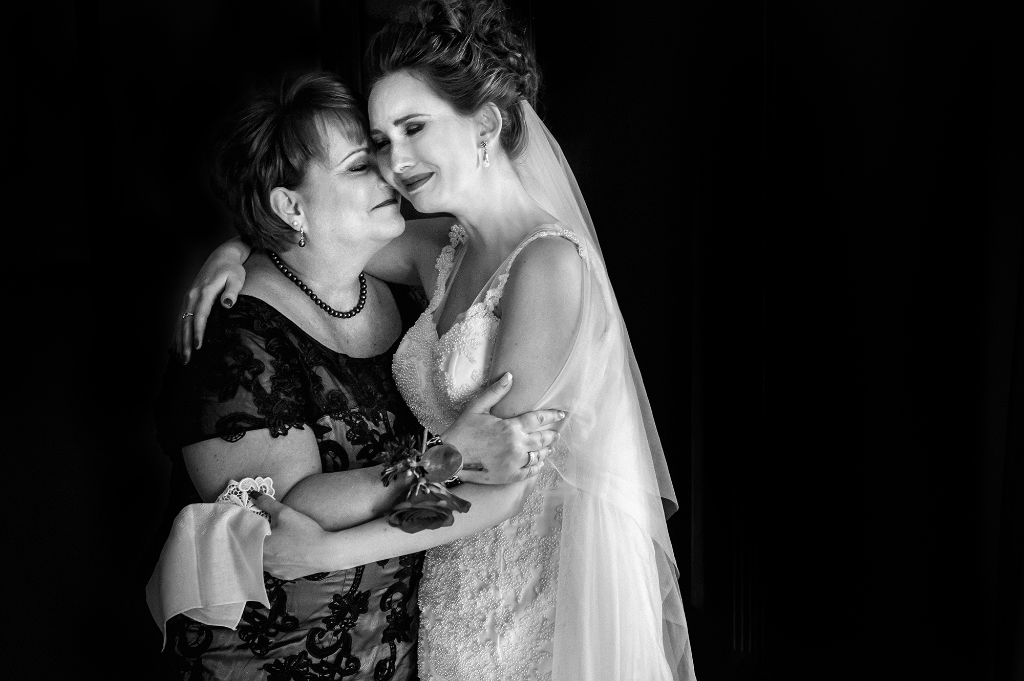 Mom and bride in tears embrace each other - photo by Davina plus Daniel