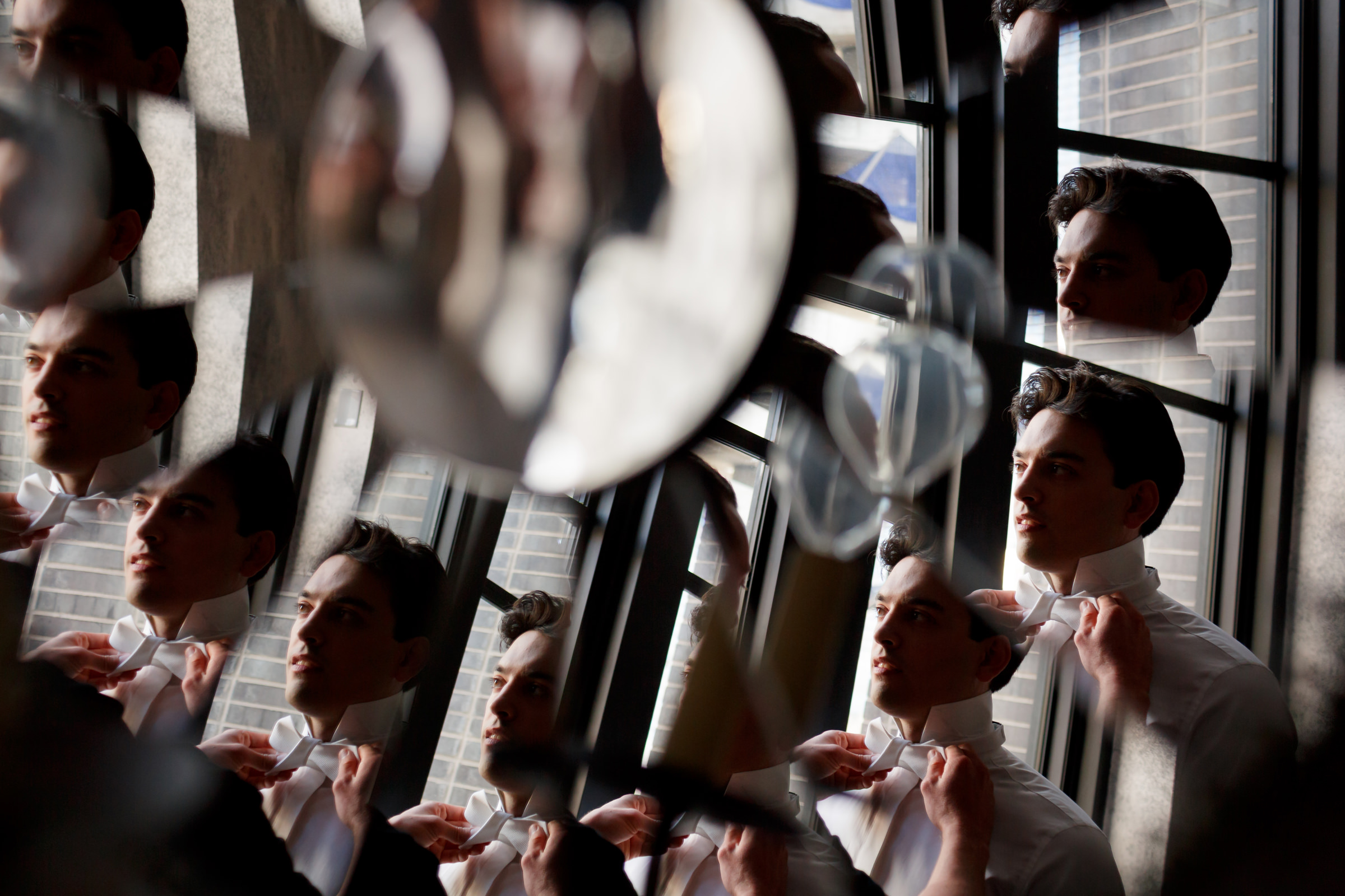 many-reflections-of-groom-putting-on-his-white-bow-tie-jenny-demarco-photography