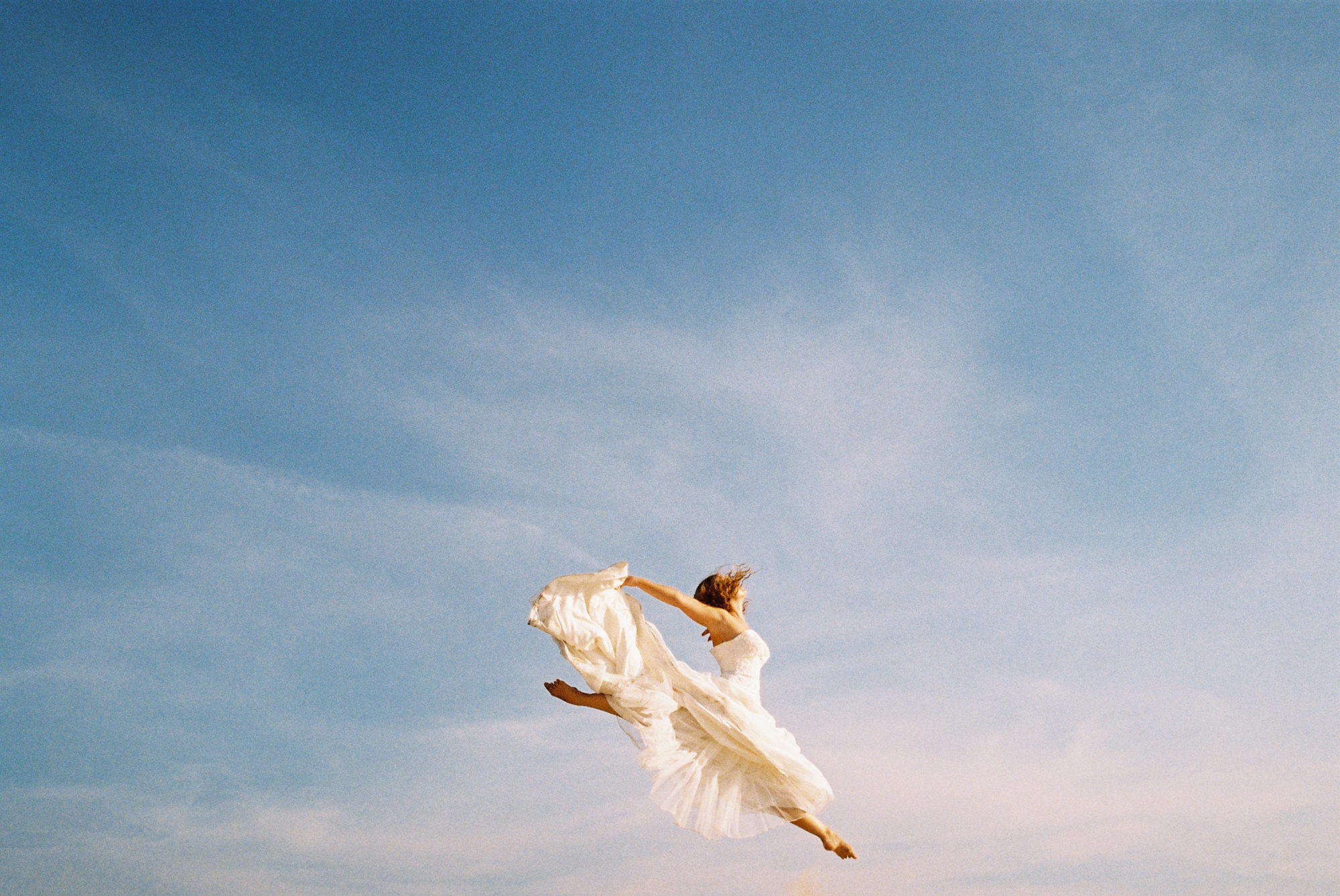 bride-in-gown-ballet-graceful-leap-in-air-against-blue-sky-worlds-best-wedding-photos-fer-juaristi-mexico-wedding-photographers