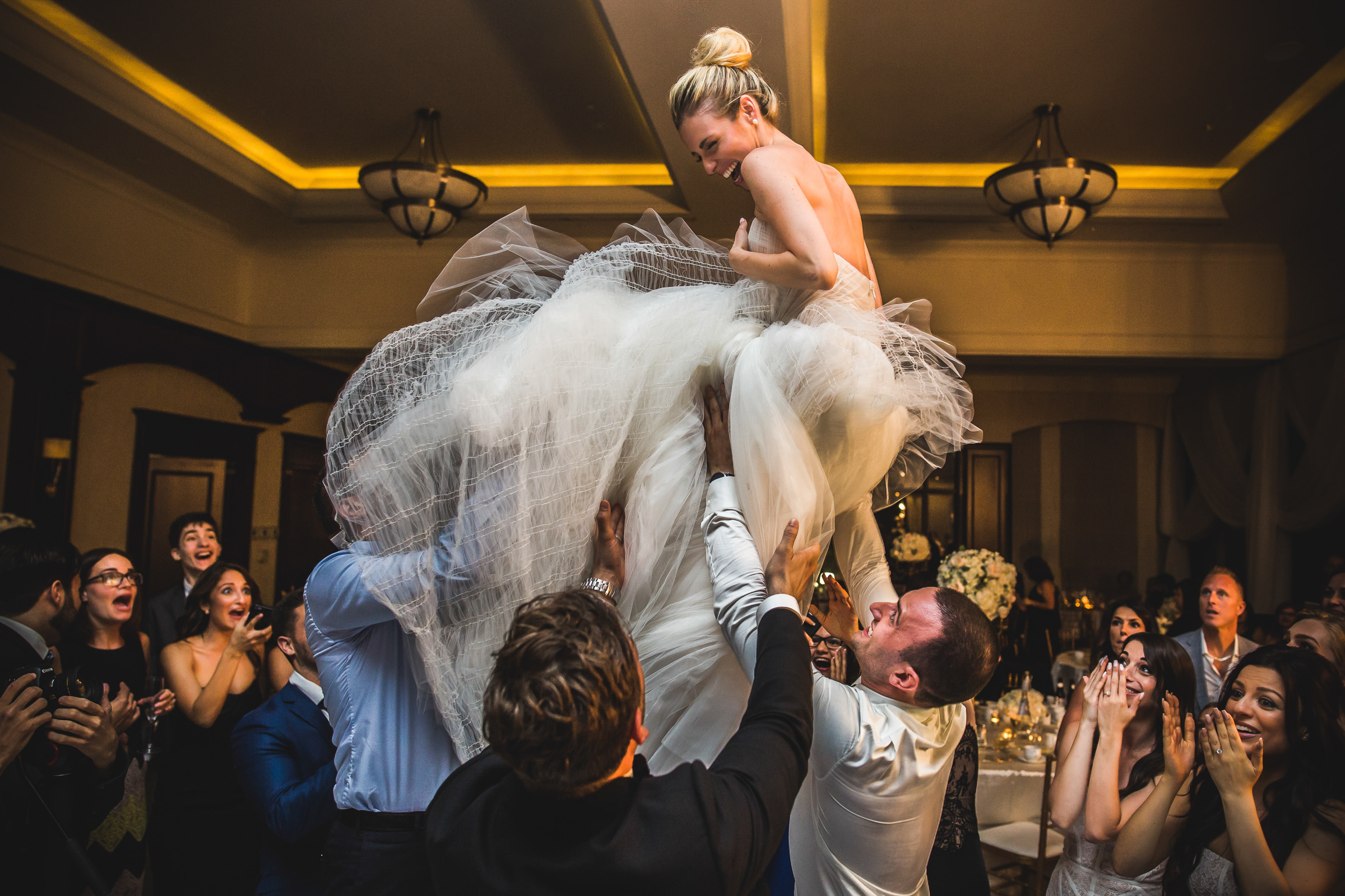 Bride being tossed in the air at reception by Marlies Hartmann of Los Angeles