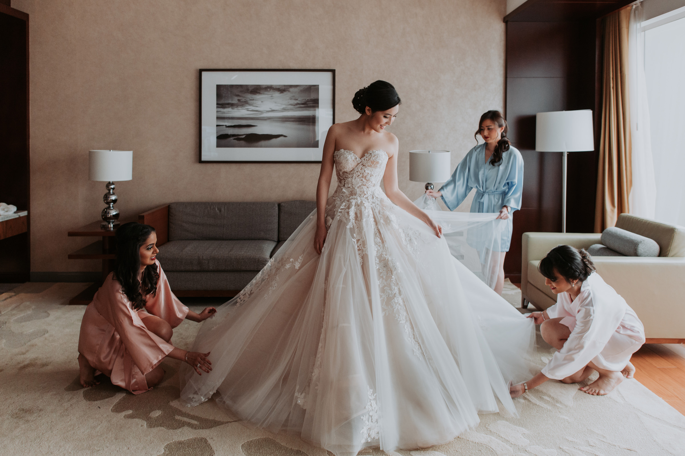 bridesmaids-assisting-bride-with-arranging-her-gown-mun-keat-studio