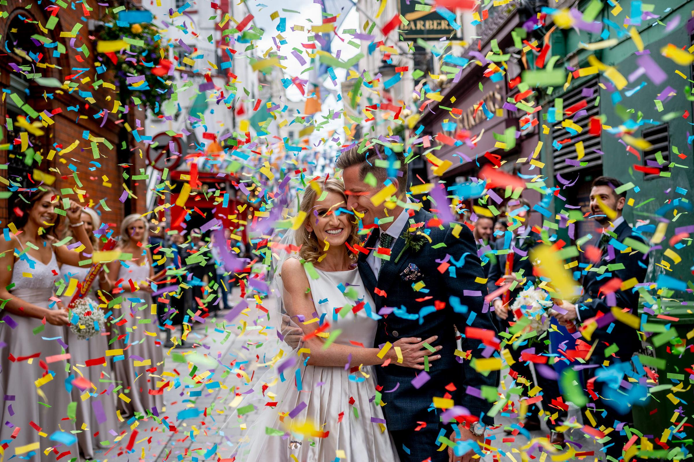 couple-exit-amid-big-colorful-confetti-john-gillooley