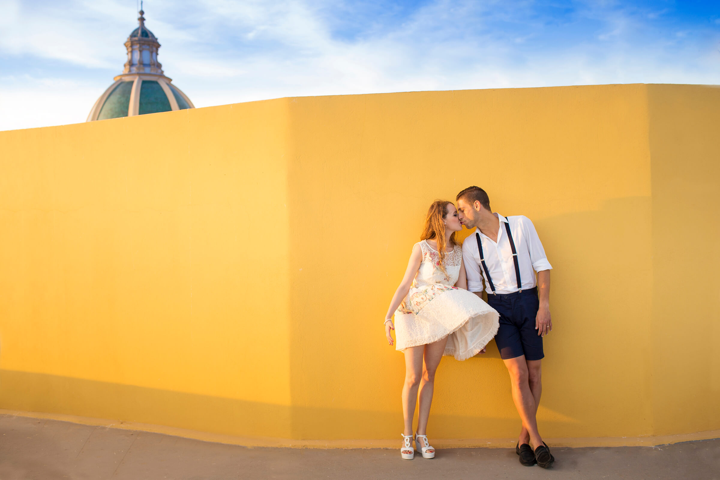 engagement-kiss-against-yellow-wall-in-italy-nino-lombardo-photographer