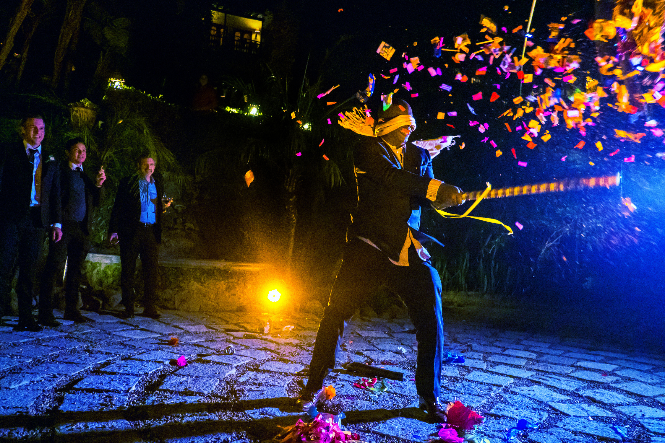 Blindfolded groom whacking pinata during wedding by Annie Bang of Los Angeles
