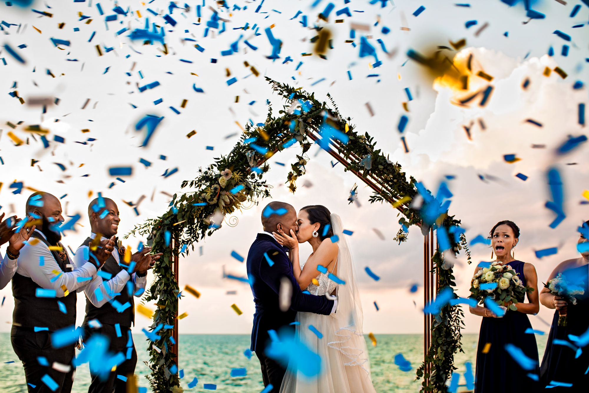 Just married couple showered with blue confetti - photo by Two Mann Studios