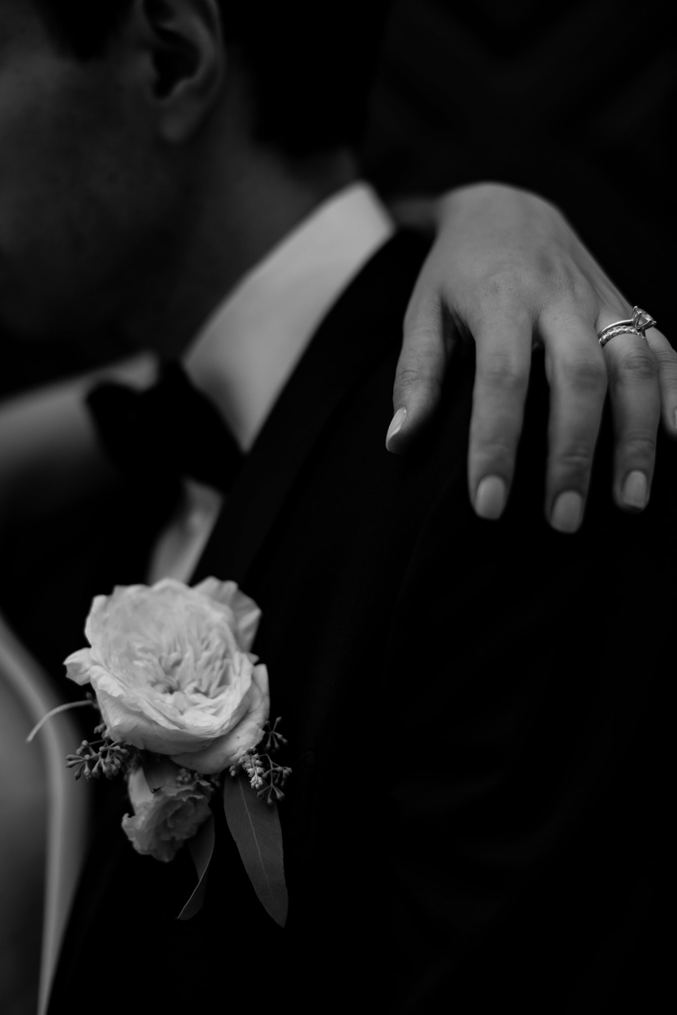 Black and white moody shot of bride's hand on groom's shoulder by Thierry Joubert