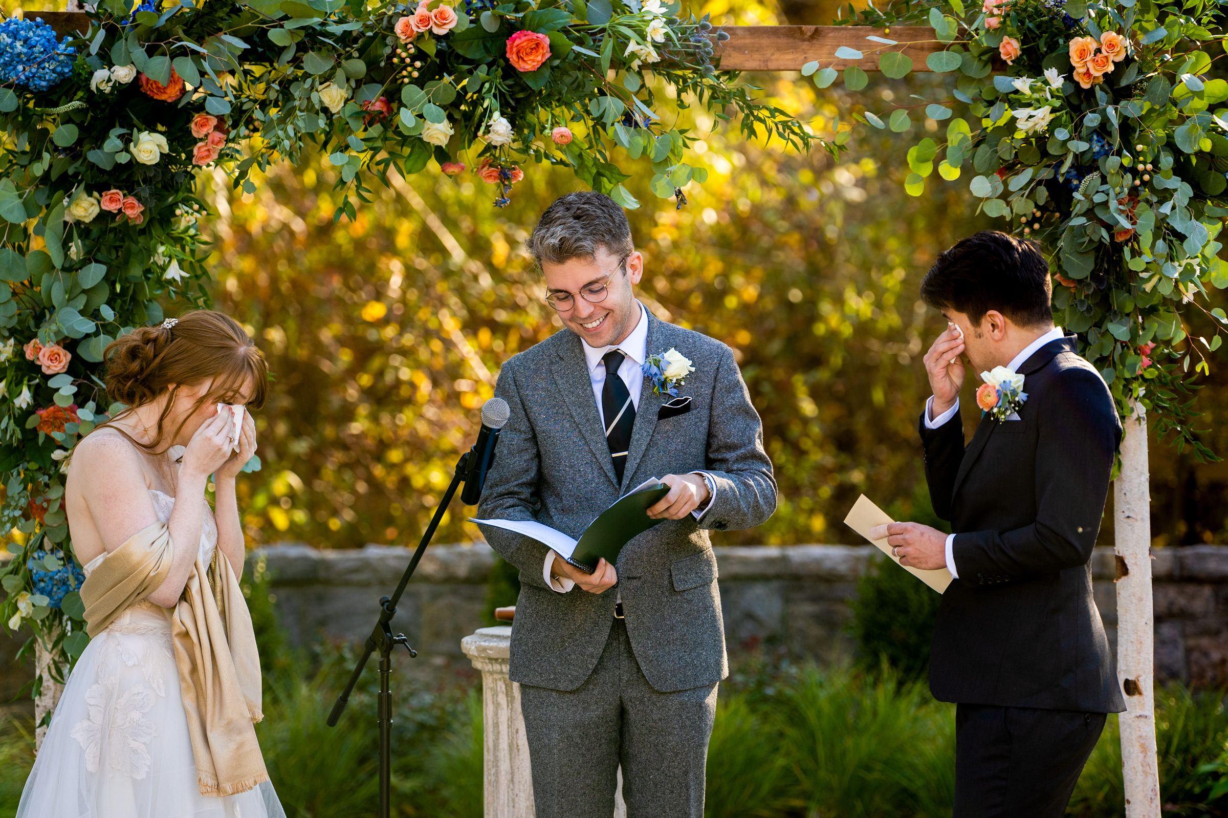 Bride and groom crying while officiant announces marriage - photo by Bee Two Sweet