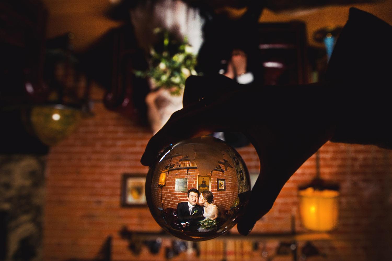 Couple portrait through a crystal ball by Callaway Gable