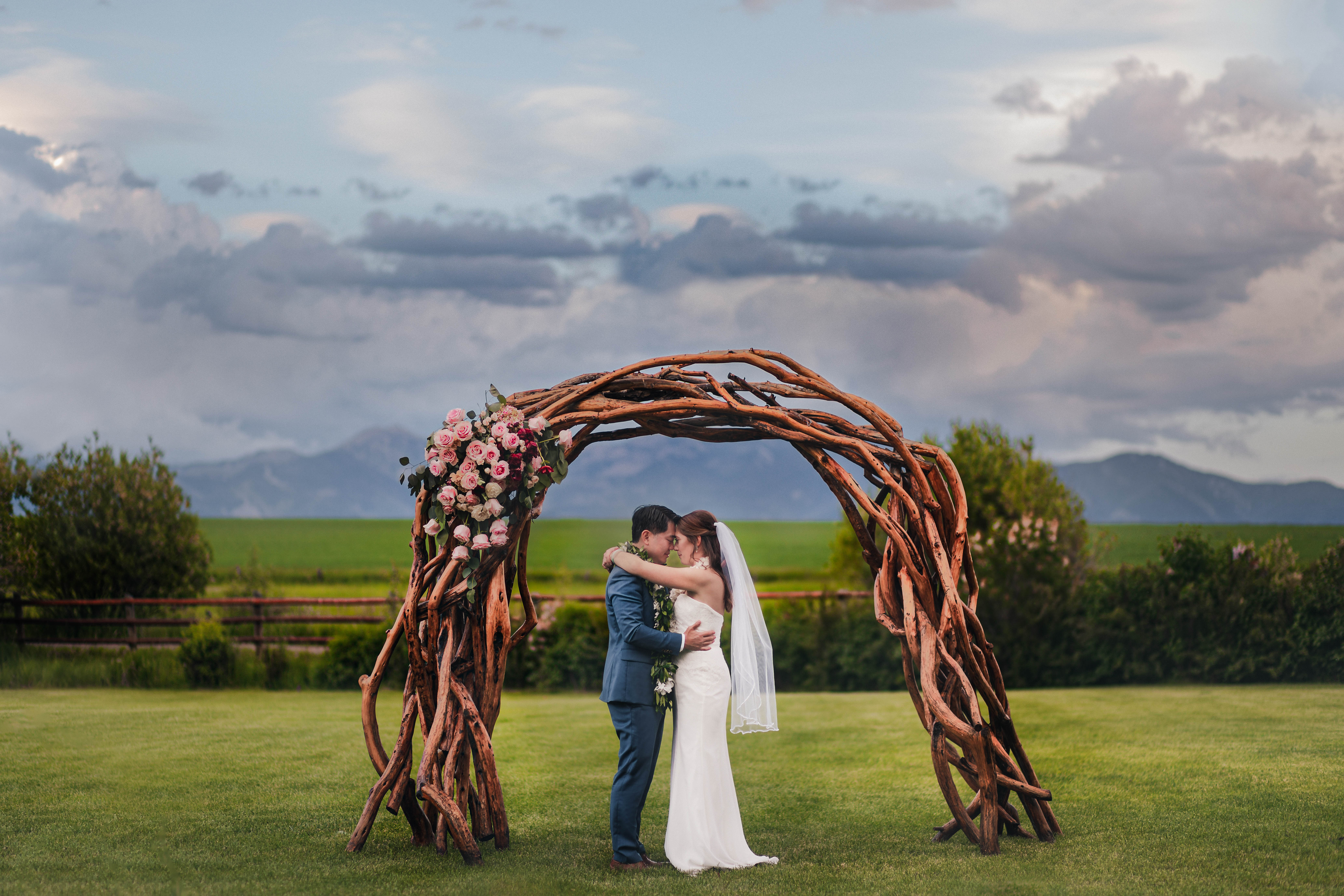 couple-under-arbor-of-branches-with-roses-adventure-wedding-photography