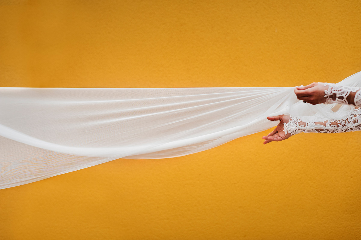 Bride's hands reaching for blowing veil - photo by Fer Juaristi