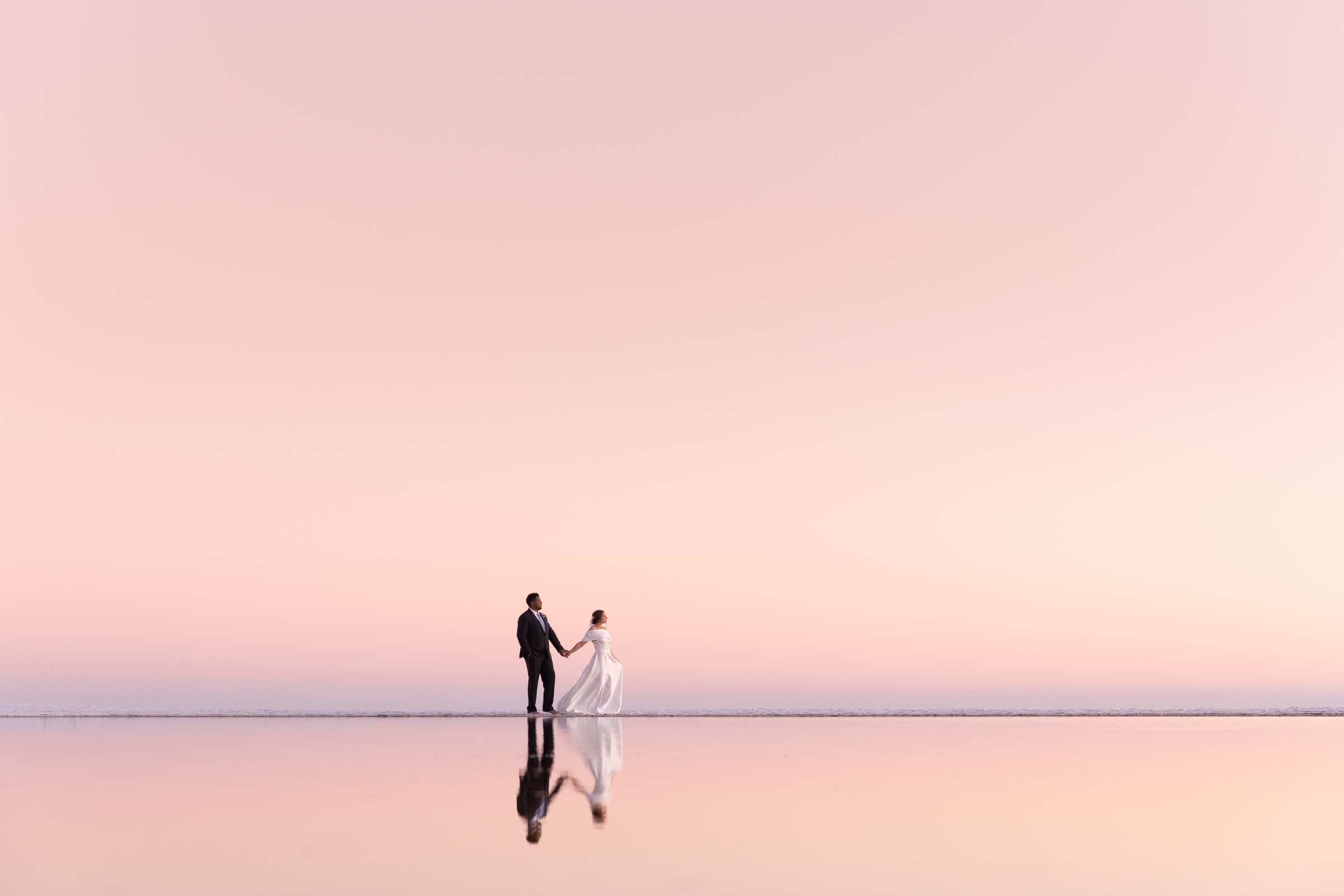 reflected-landscape-couple-against-pink-sky-modernmade-weddings