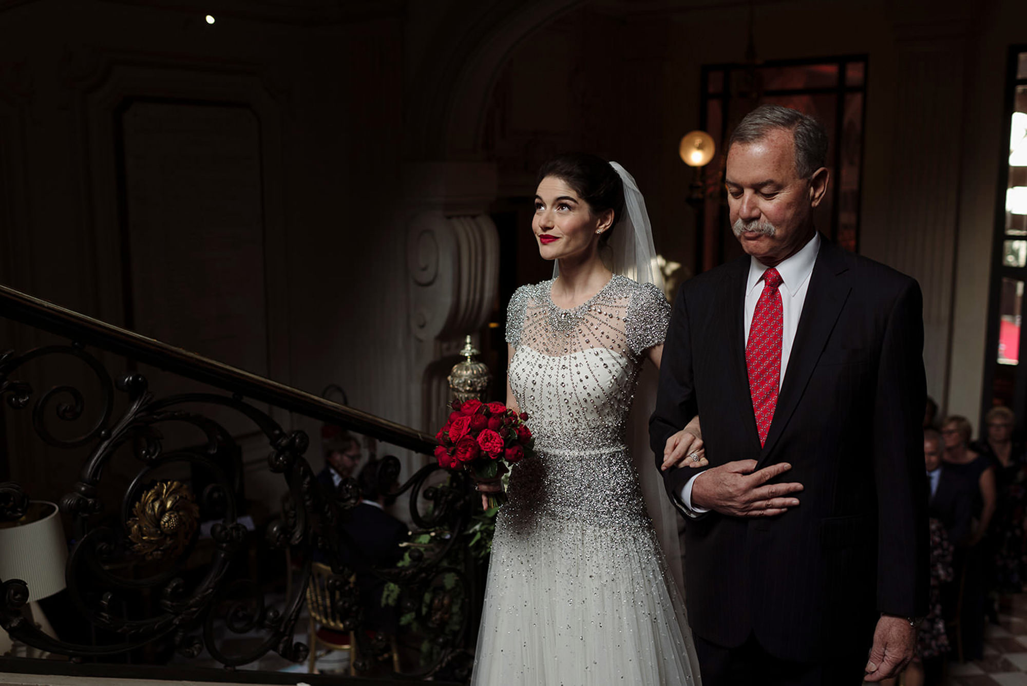 Bride in beaded gown heads to the aisle with her father - photo by Thierry Joubert