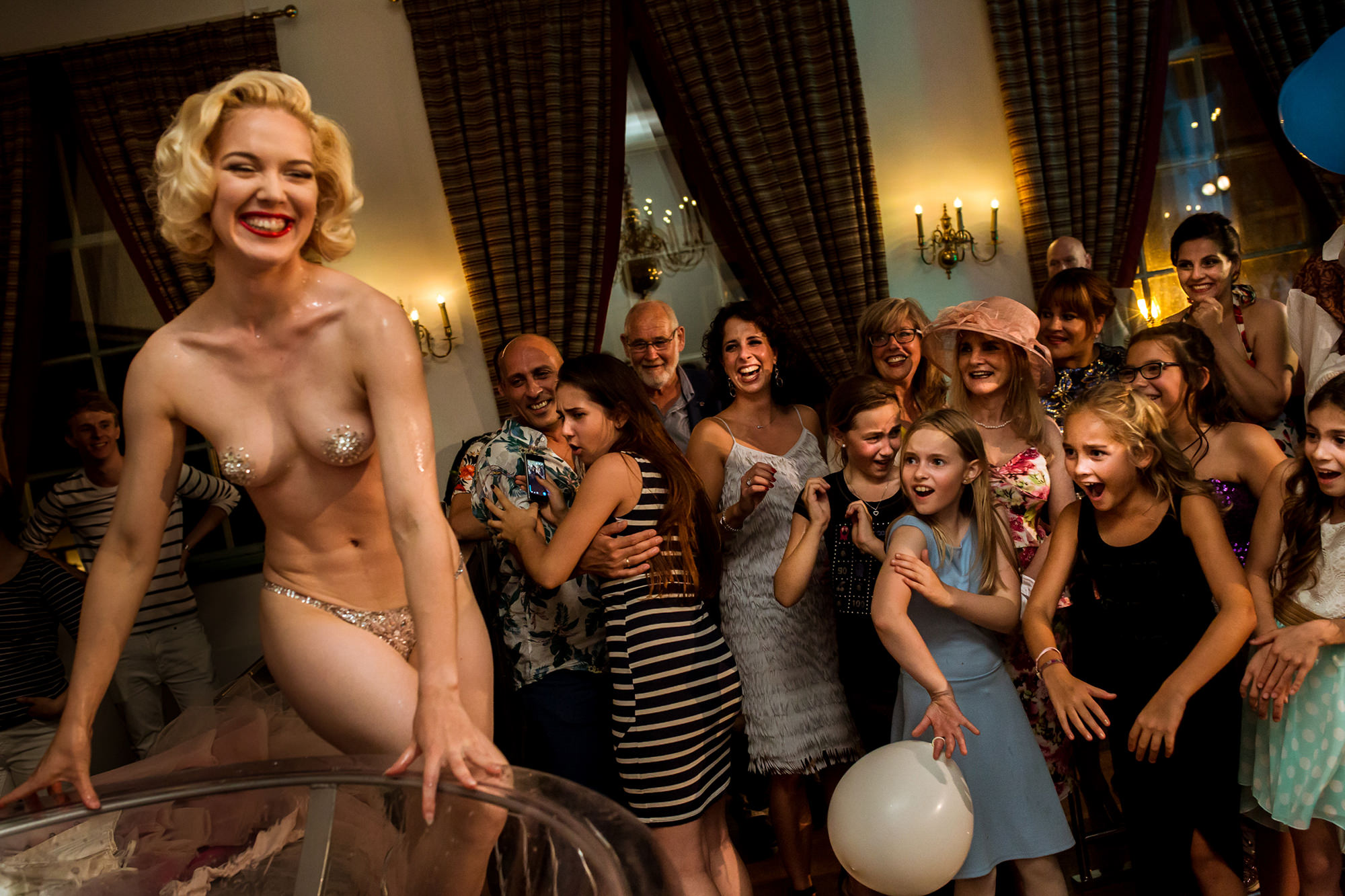 guests-and-young-girls-reacting-to-burlesque-dancer-on-table-worlds-best-wedding-photos-fotobelle-netherlands-wedding-photographers