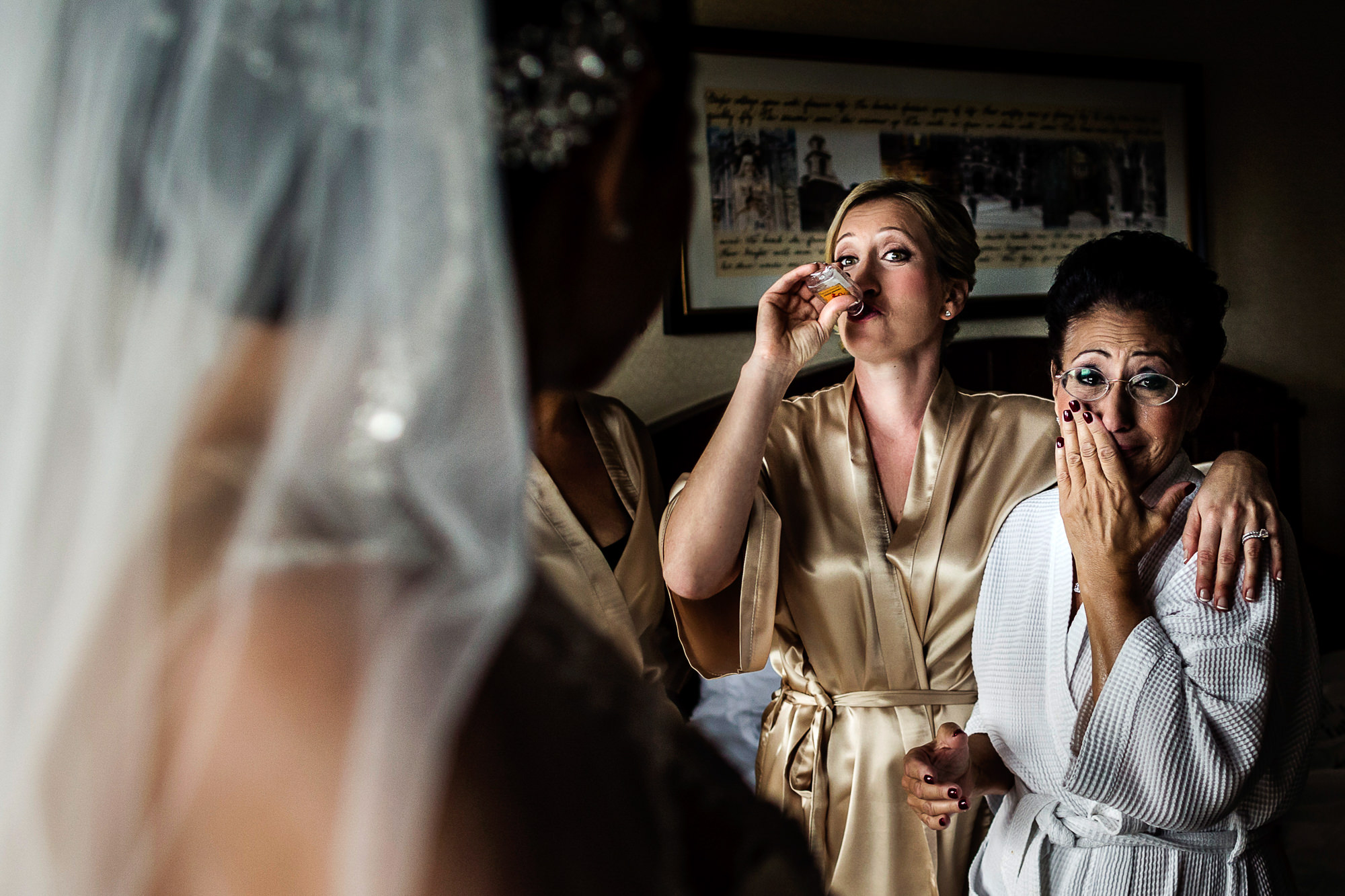 Mom and sister drinking and crying while bride gets ready - photo by Jag Studios