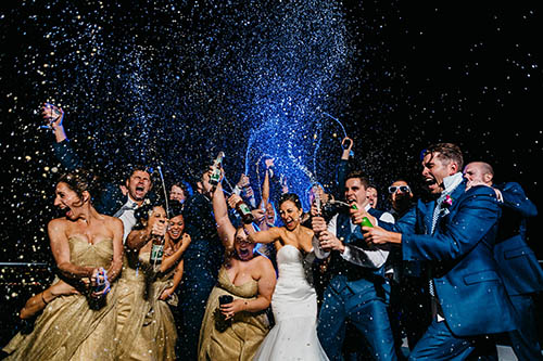 wedding party celebrating and popping champagne - photo by Ken Pak