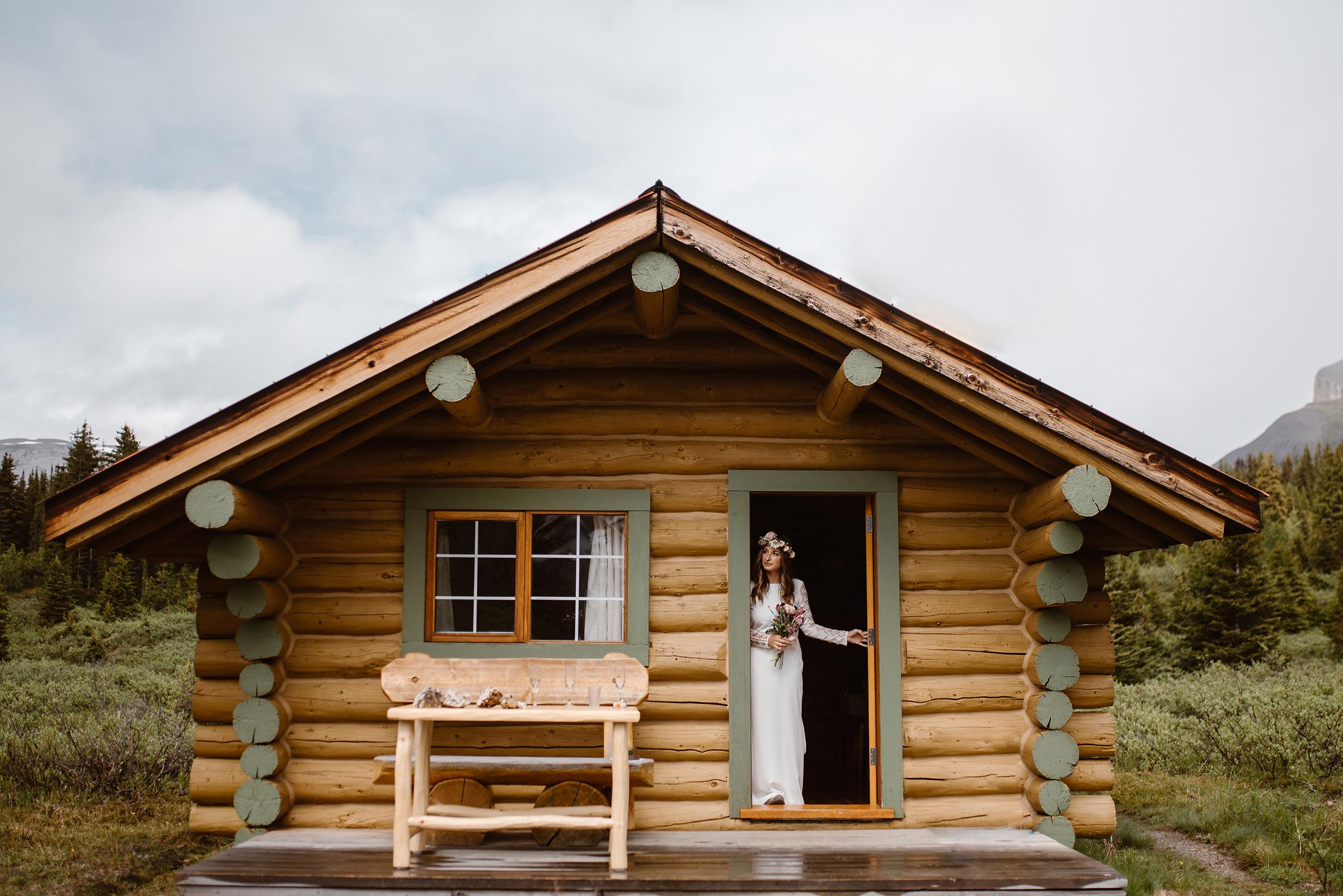 Mount-Assiniboine-provincial-Park- Alberta- Canada-bride-peeks-out-of-log-cabin-door-virginia-evan