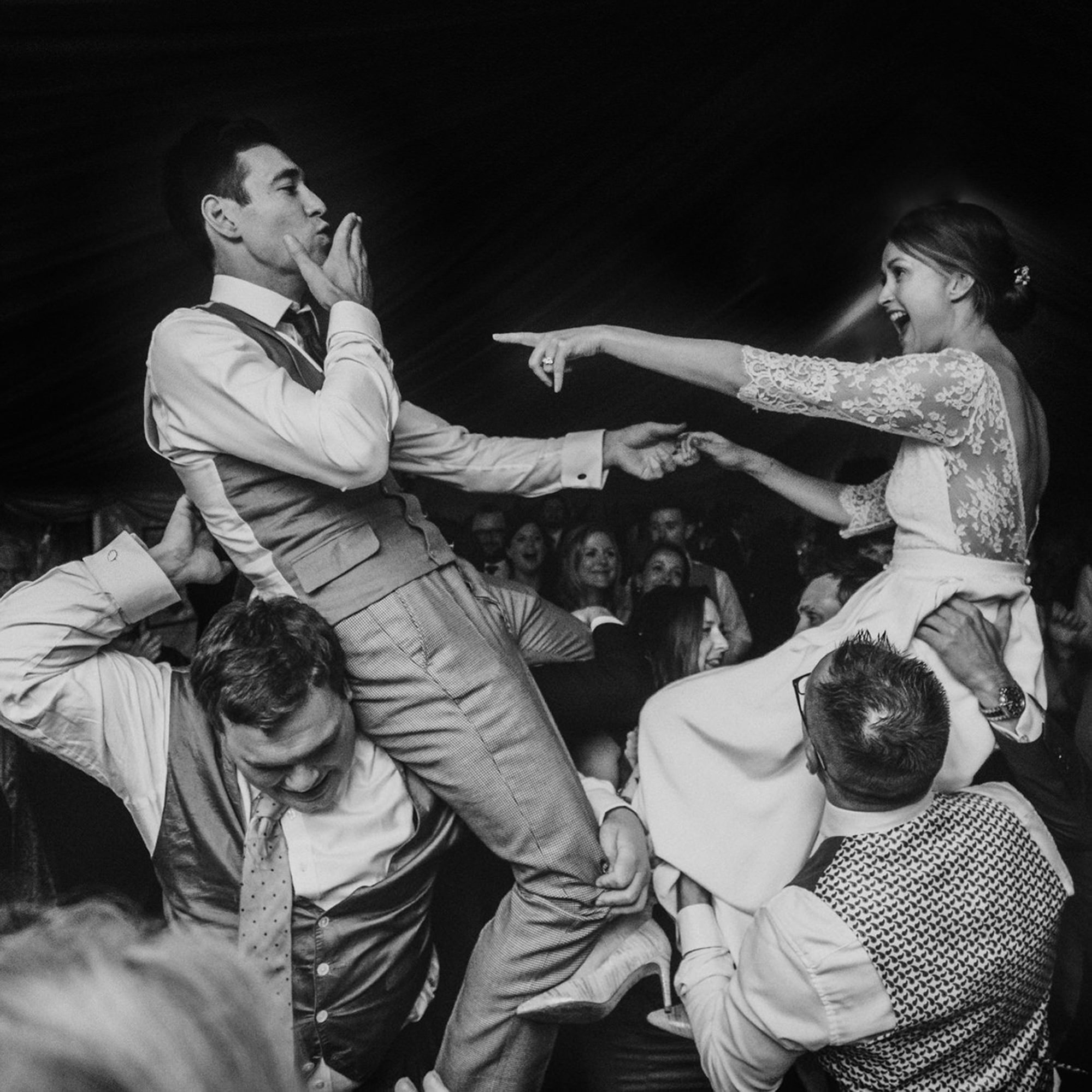 bride-and-groom-held-up-by-friends-partying-at-reception-by-miki-studios