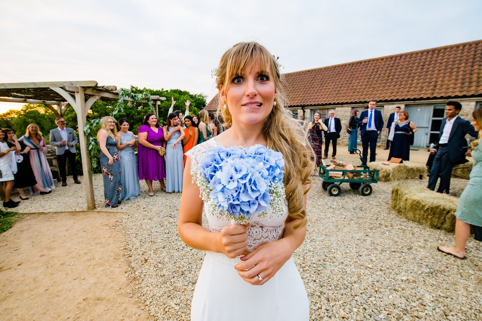 Hesitant bride gets ready to throw her hydrangea bouquet - photo by Rich Howman - UK wedding photographer